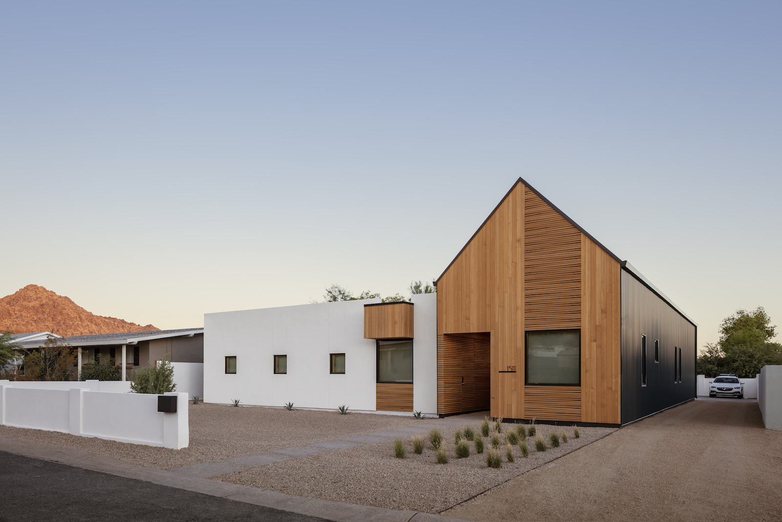 House in the desert has a gabled roof on one end and flat roof on the other. If features a white and wood exterior.