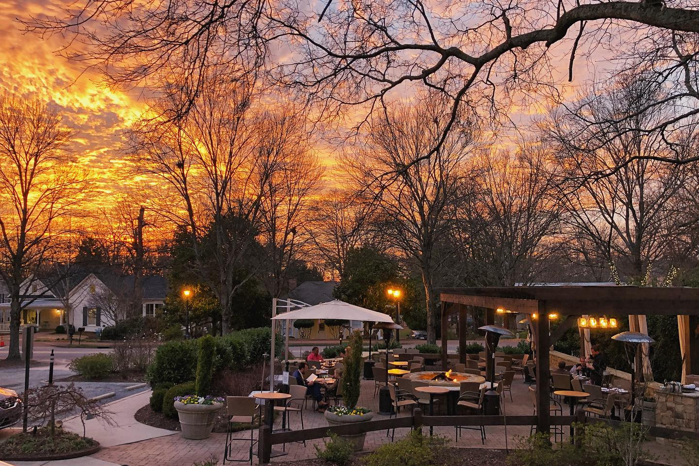 Clouds lit up by the fiery sunset on a winter's evening in Roswell, Georgia, as people dine on the stone patio around the fire pit at Osteria Mattone