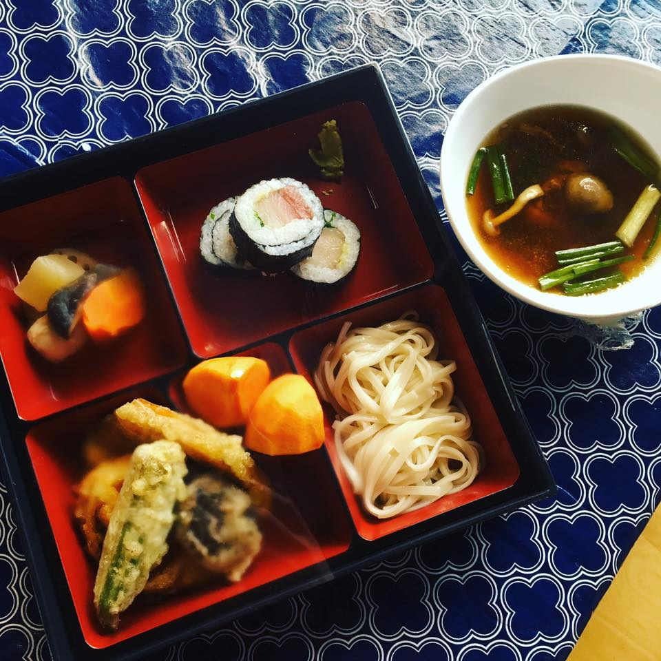 A Japanese bento box lunch sits on a patterned blue tablecloth. The box includes sushi, tempura, noodles, and more, and a small bowl of soup is off to the side.