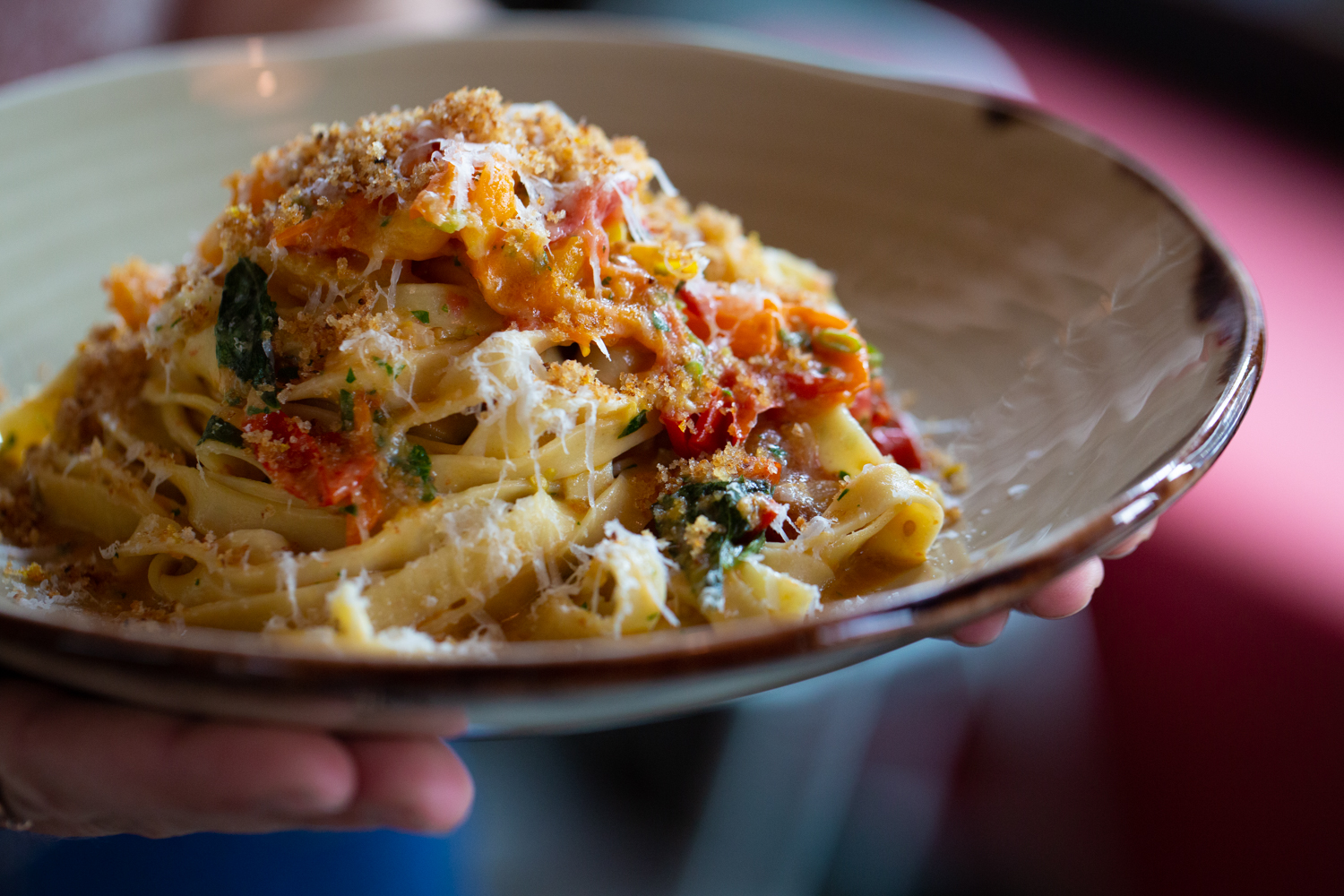 A picture of a Trifecta Tavern server holding a bowl of pasta with cheese and vegetables