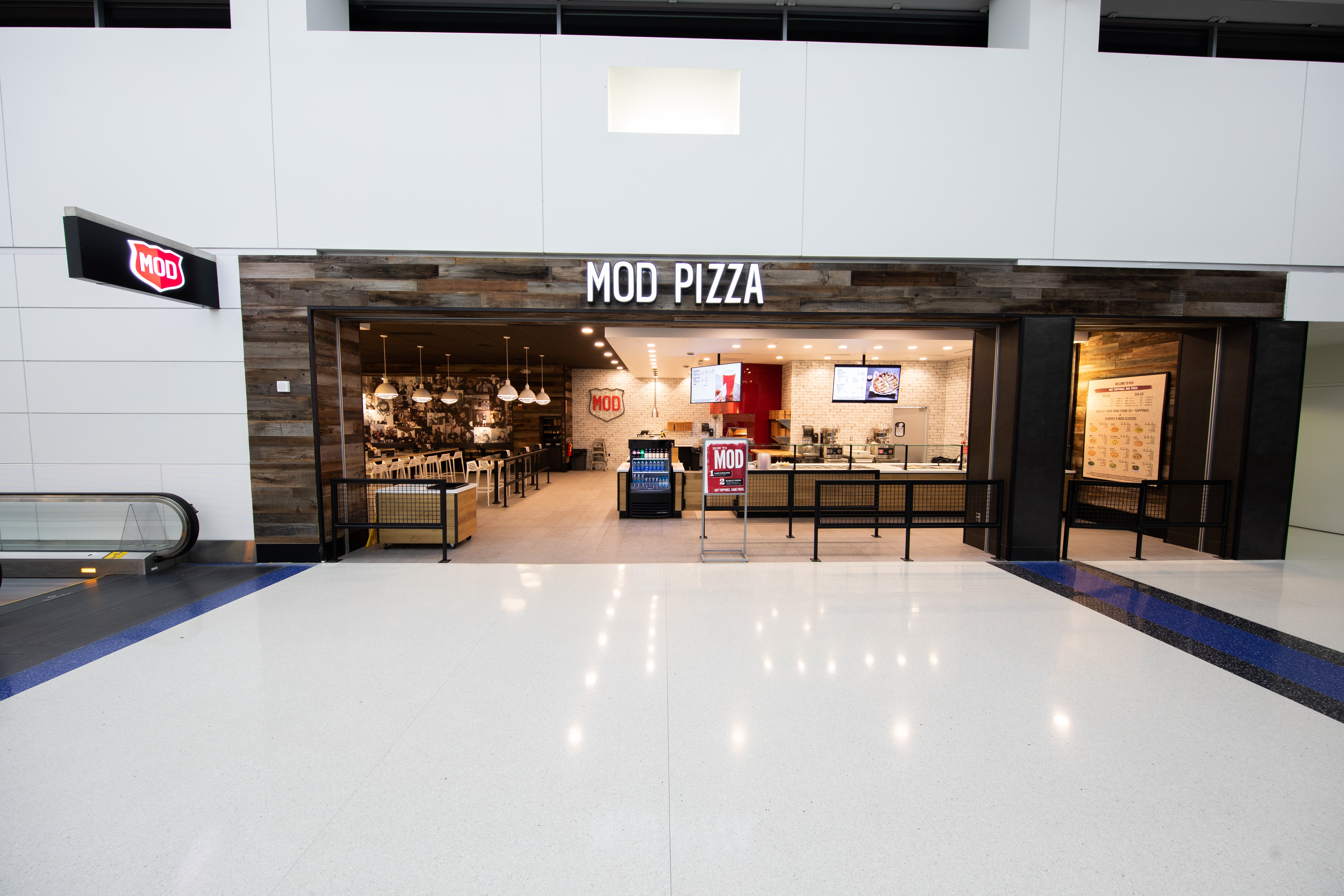 A photo of the wood-paneled storefront for Mod Pizza in the white-walled North Terminal.