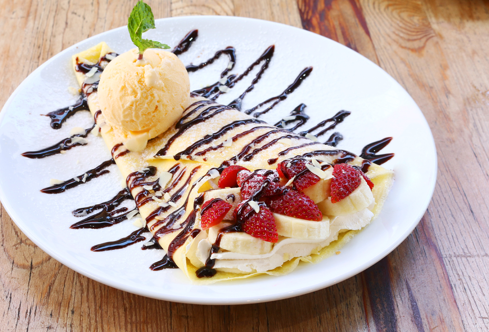 Closeup of vanilla ice cream with crepes and strawberry served at Crepe Station.