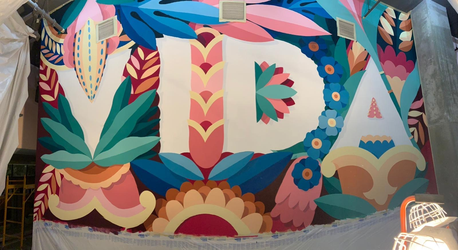 """An unfinished mural with the word """"Vida"""" surrounded by tropical flowers and plants"""