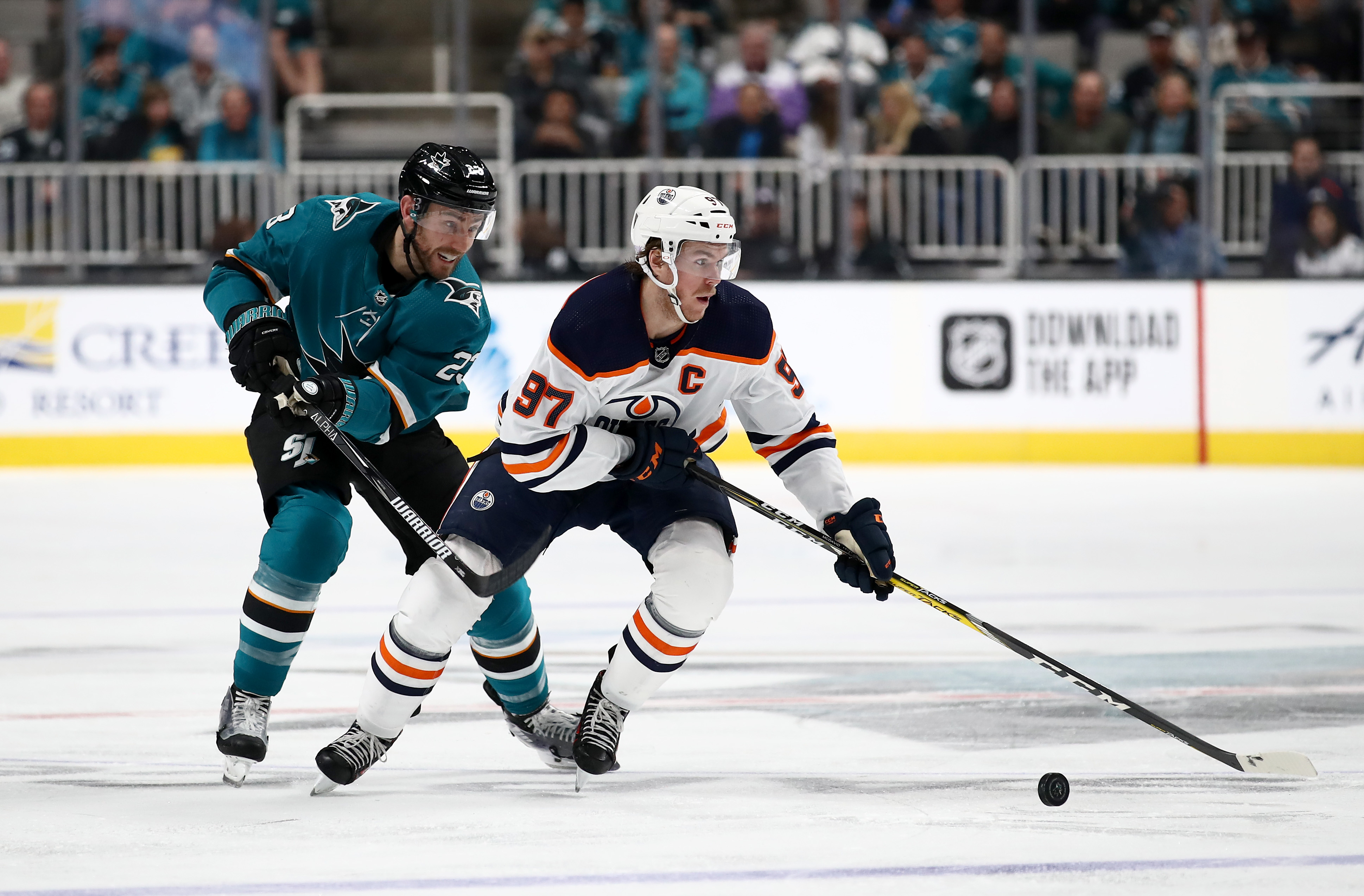Connor McDavid #97 of the Edmonton Oilers tries to skate away from Barclay Goodrow #23 of the San Jose Sharks at SAP Center on November 12, 2019 in San Jose, California.