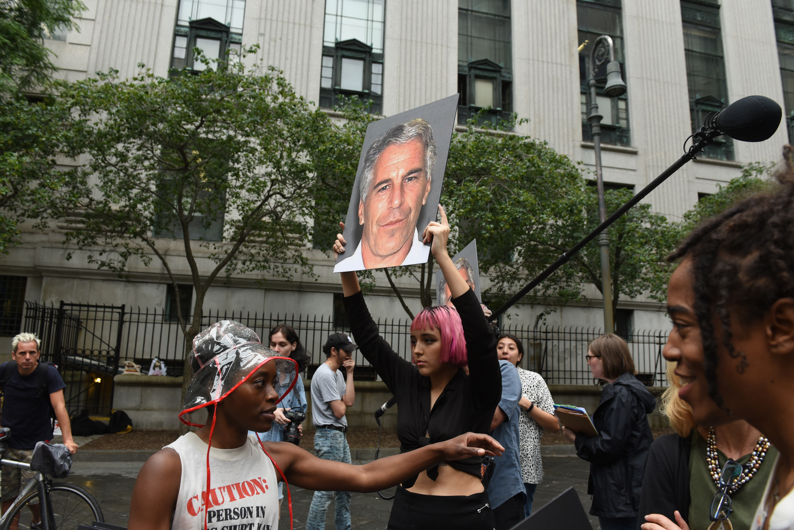 Protesters, including one holding a sign with a photograph of Jeffrey Epstein's face.