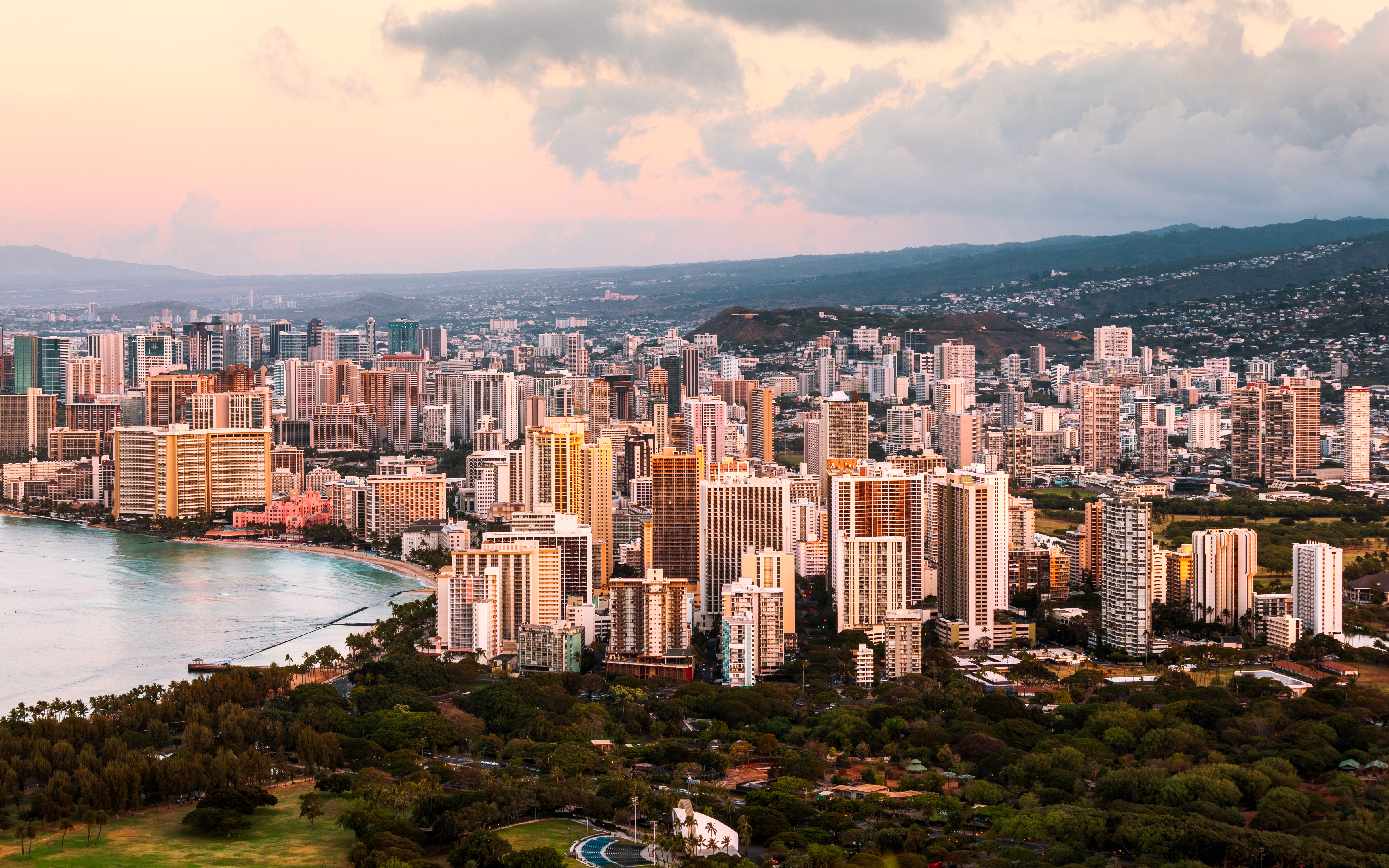 Honolulu skyline featuring high-rises and mountains in the distance.