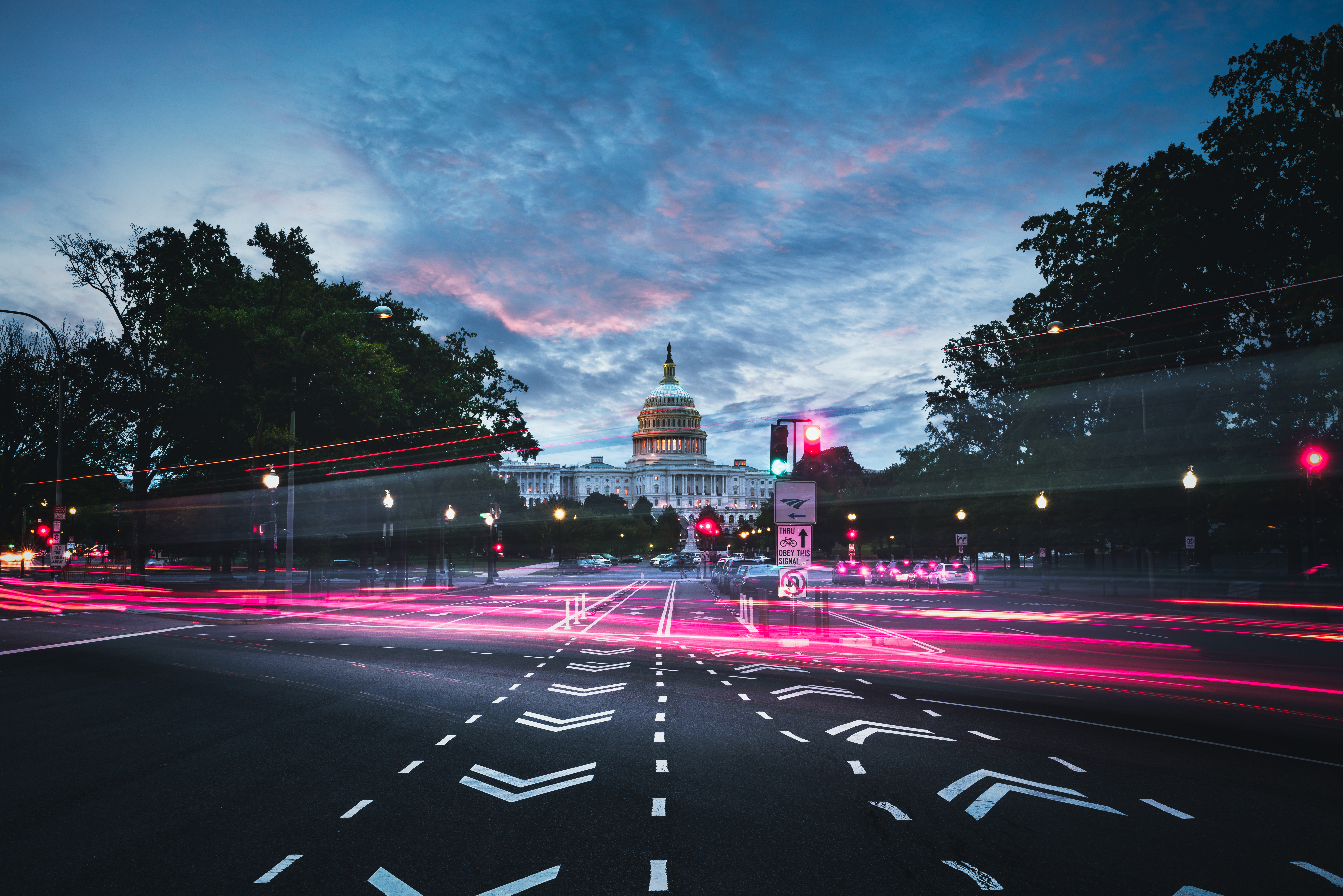 The light trail from cars speeding through an intersection near a federal capital building. Two bike lanes go through the intersection in either direction.
