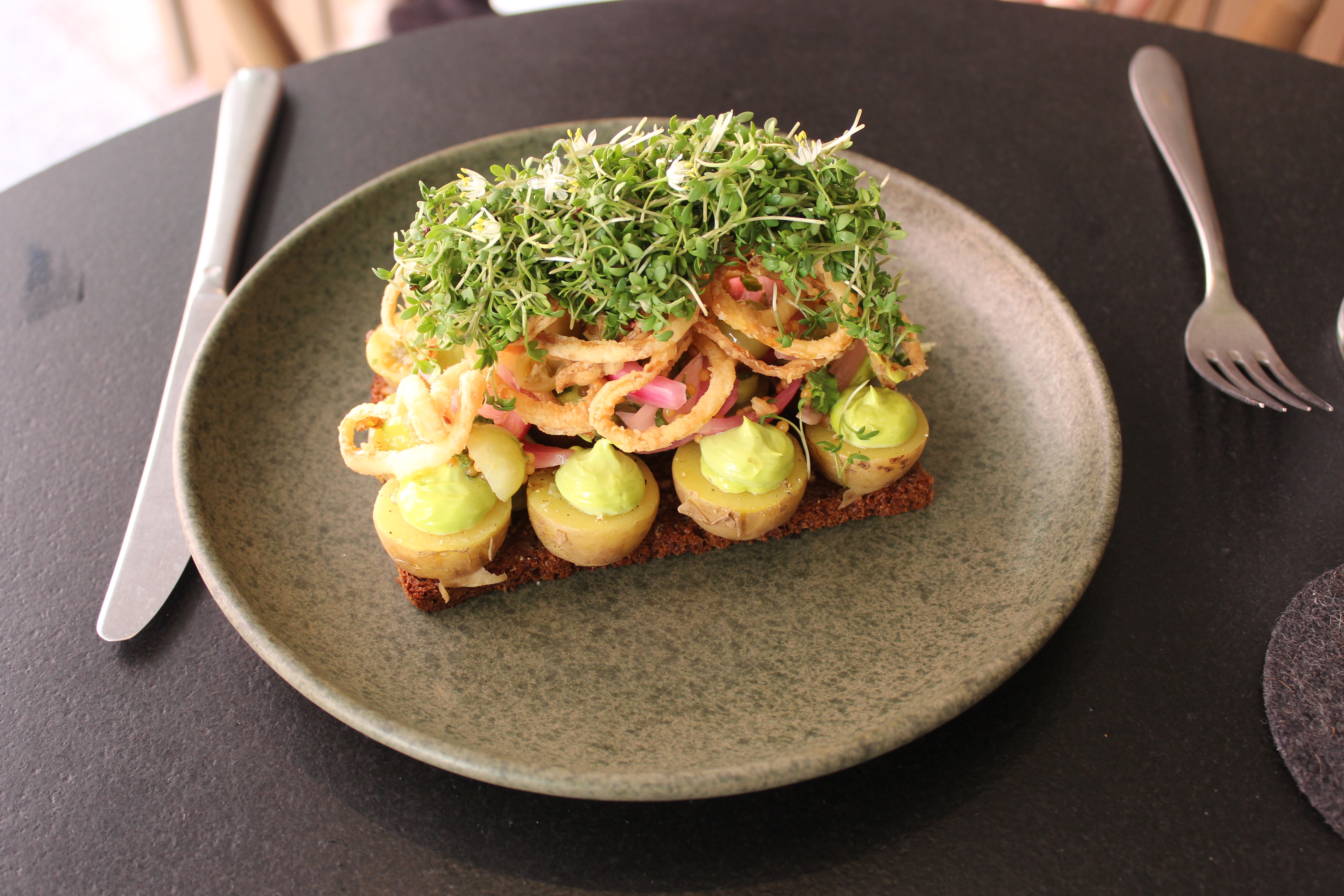 An open-faced smorrrebrod sandwich of dark rye bread topped with a towering display of deviled eggs, fried onions and sprouts, sitting on a slate plate on top of a simple black tabletop with cutlery on either side.