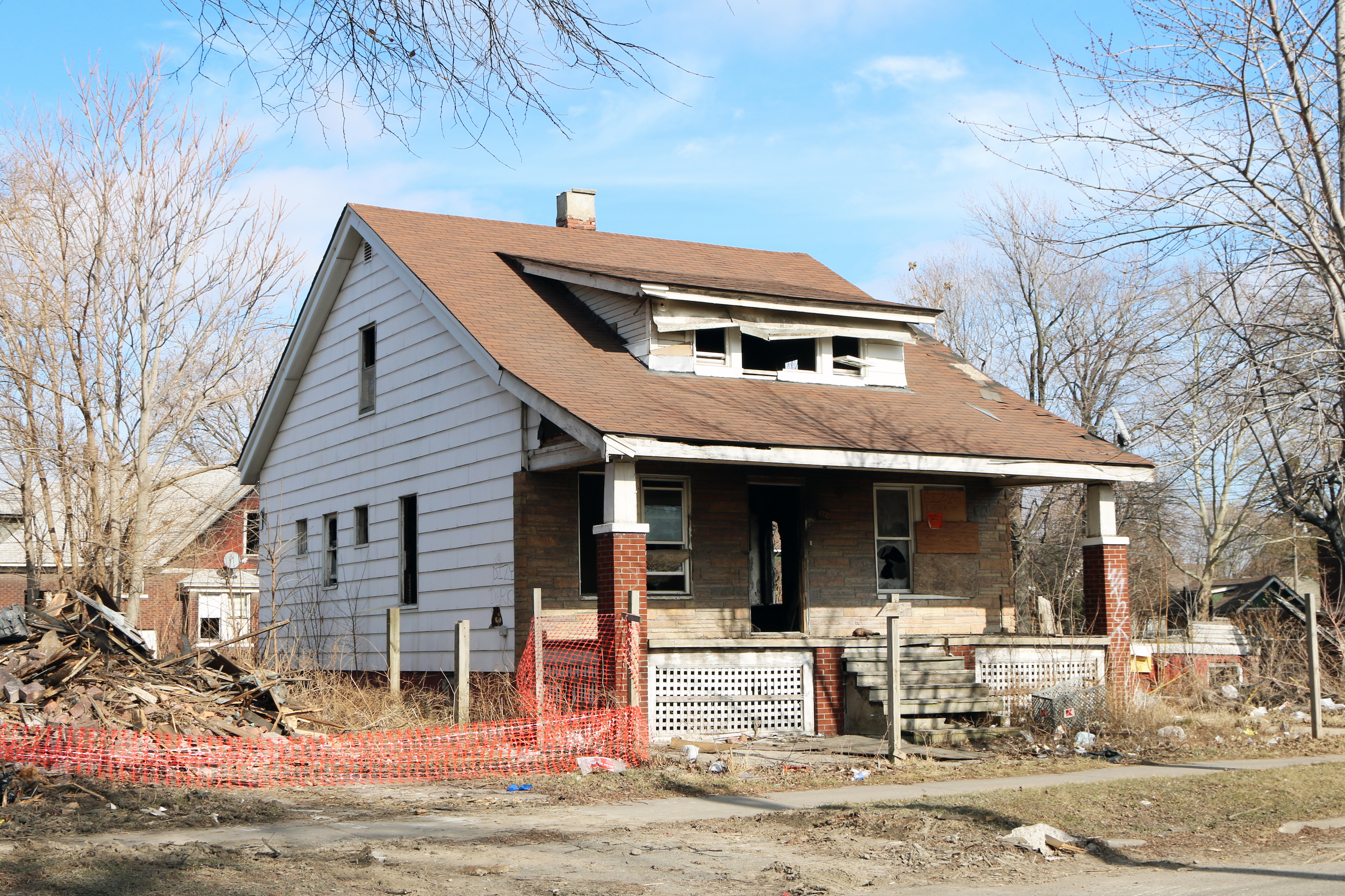 An abandoned home with no windows and red tape around a demolished home next door.