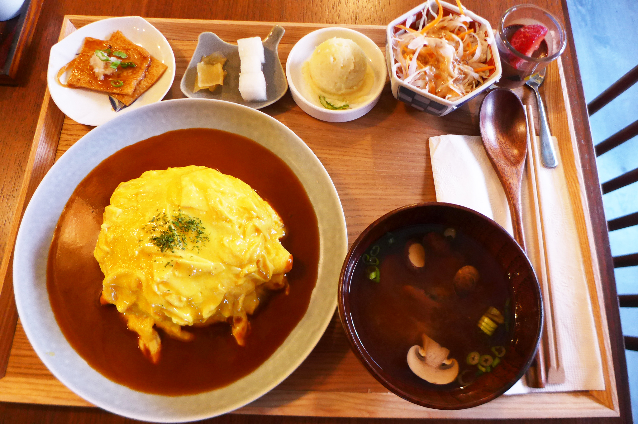 A tray is covered with small dishes, the largest of which is a very yellow omelet in a pool of brown gravy.
