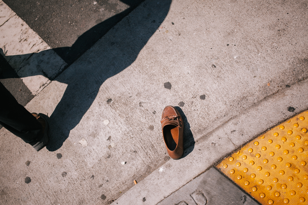 A single brown shoe lying in the gutter on a San Francisco street.