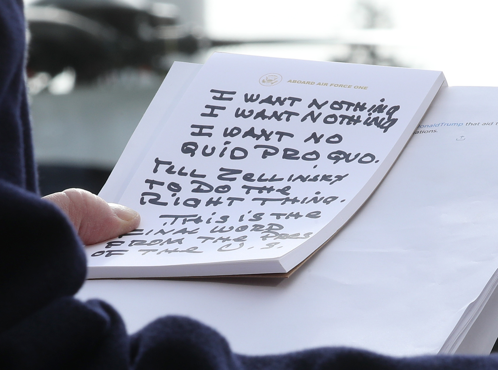 President Trump holding a notepad covered in notes written in black ink.