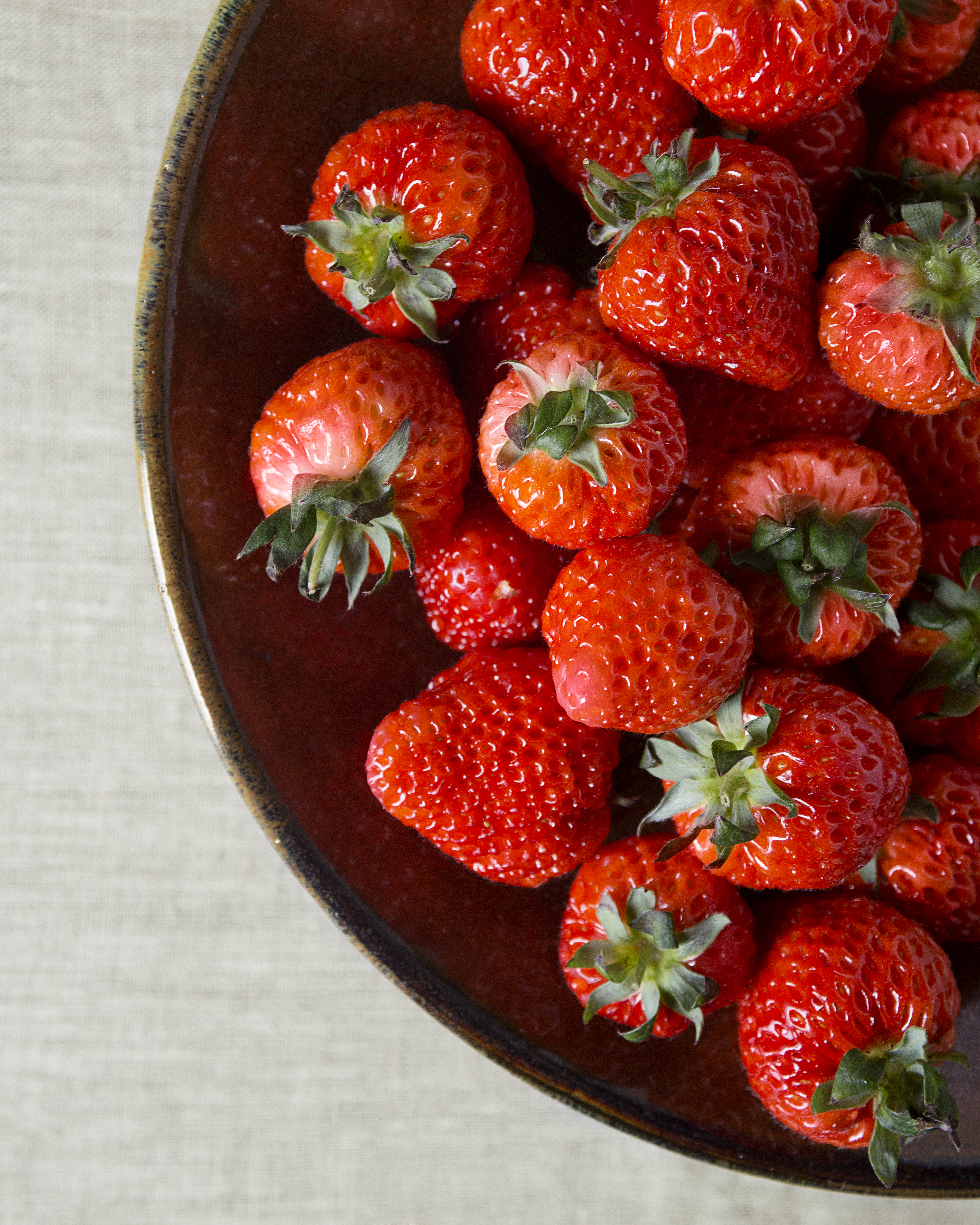 A brown bowl filled with strawberries.