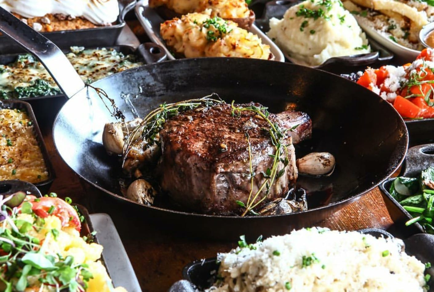 A cast iron skillet with a large steak surrounded by sides of mashed potatoes, rice, and vegetables