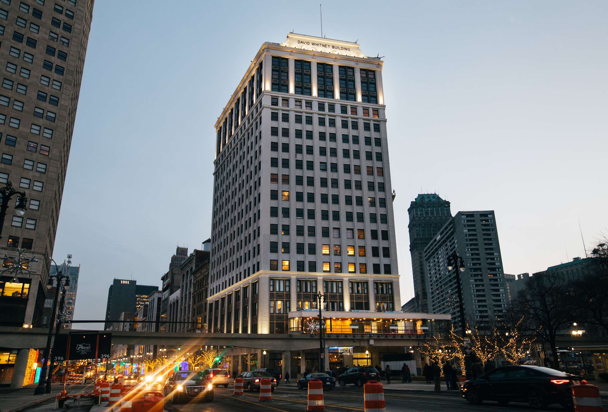 """A wide, white skyscraper. At the top in red letters reads """"David Whitney Building."""""""