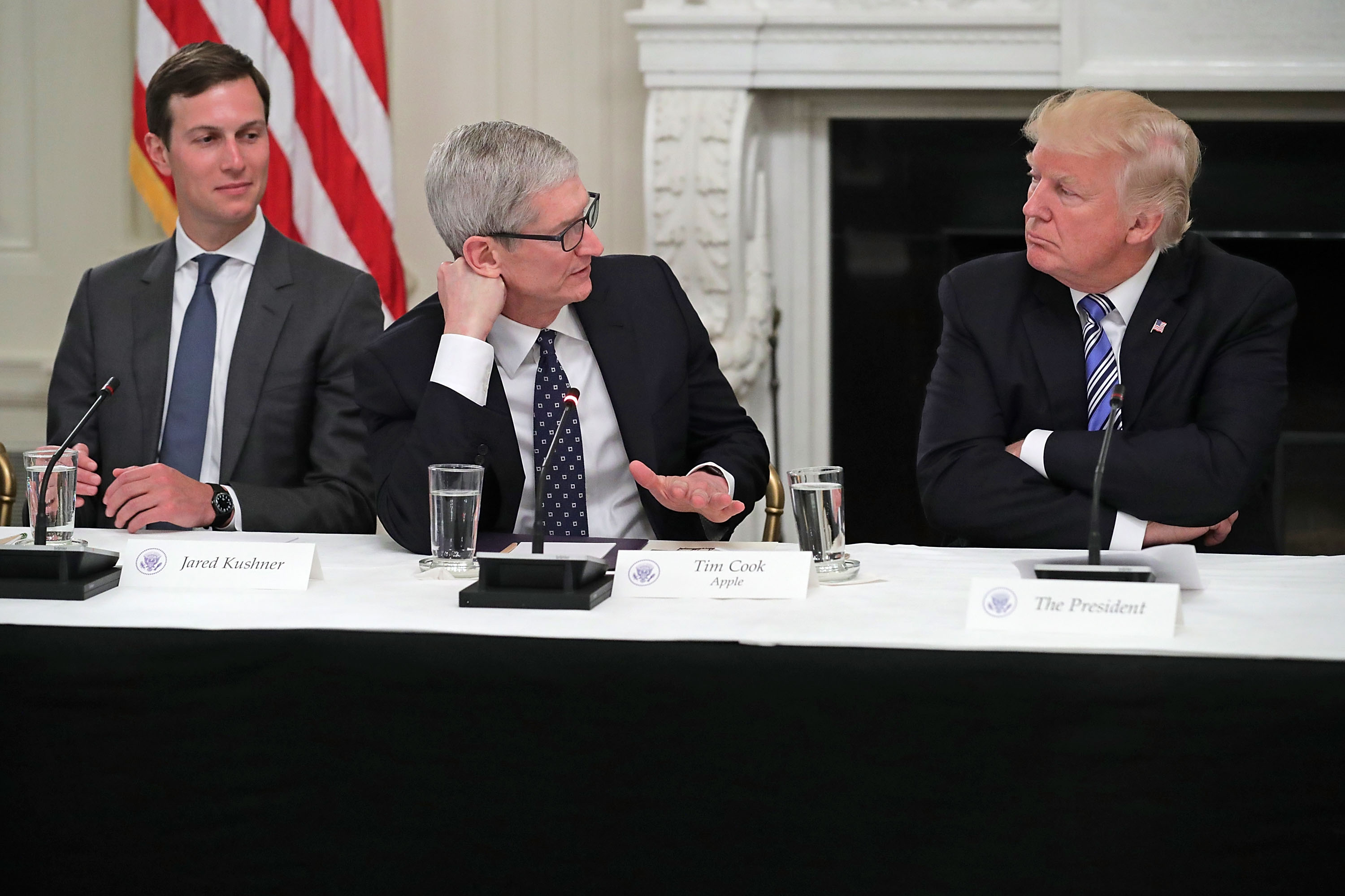 Apple CEO Tim Cook talks to President Donald Trump as the president's son-in-law, Jared Kushner, looks on.