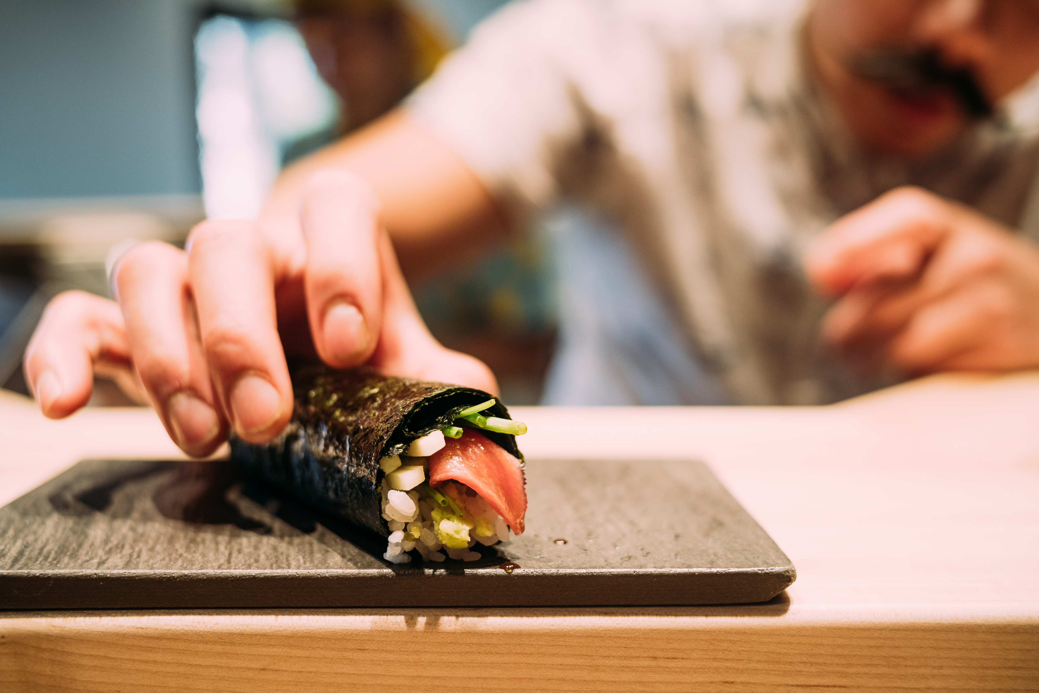 A chef places a crab-stuffed handroll on a serving plate