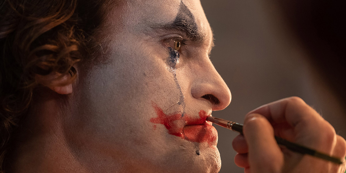 "Joaquin Phoenix applying face paint in the movie ""Joker."""