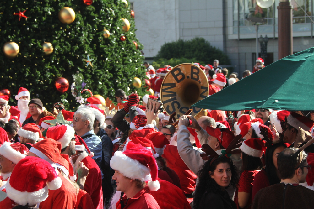 A crowd of dozens of people dressed in red and white Santa Claus costumes, one of them carrying a tuba.