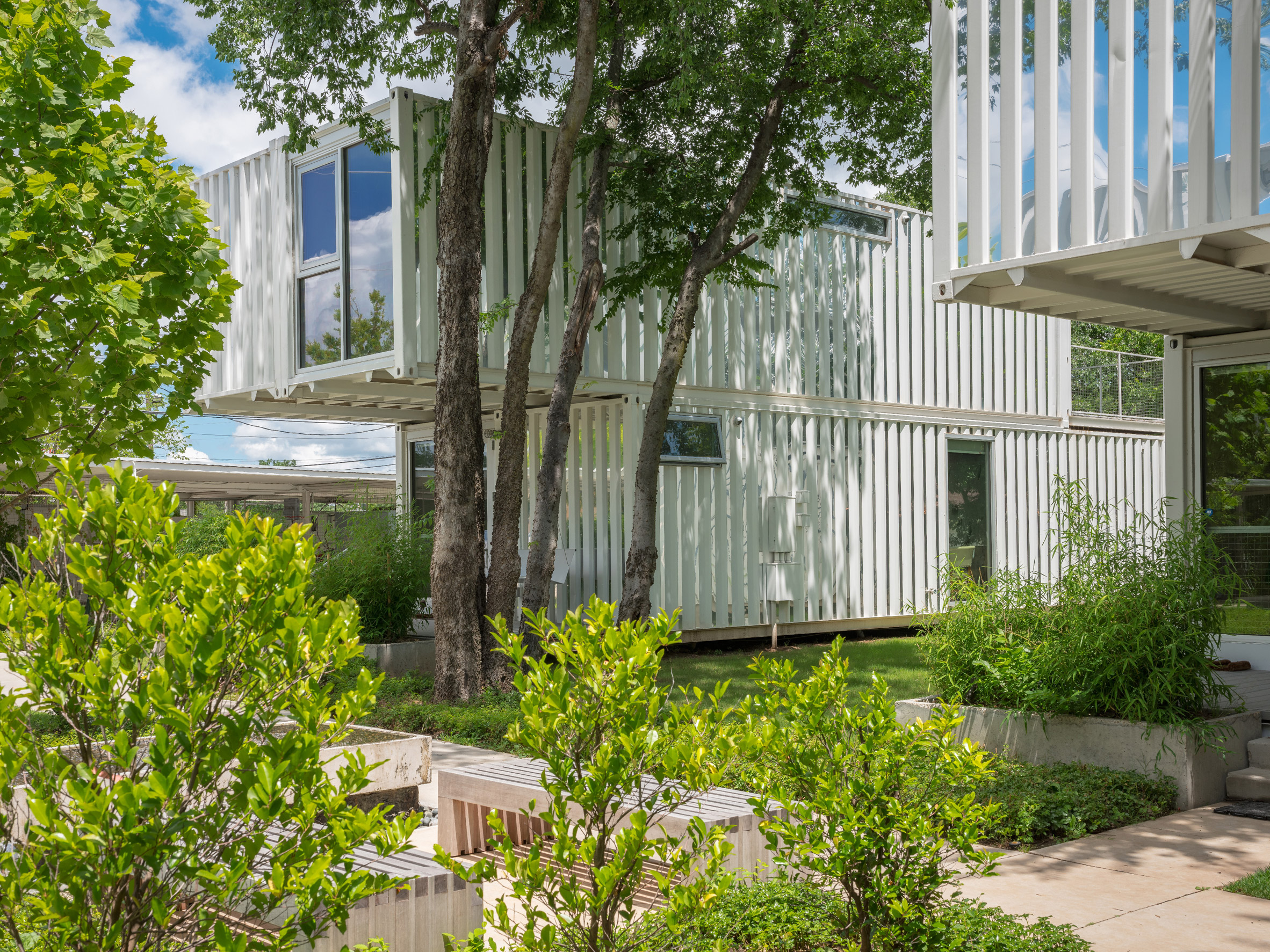 Homes built from white shipping containers surrounded by trees.