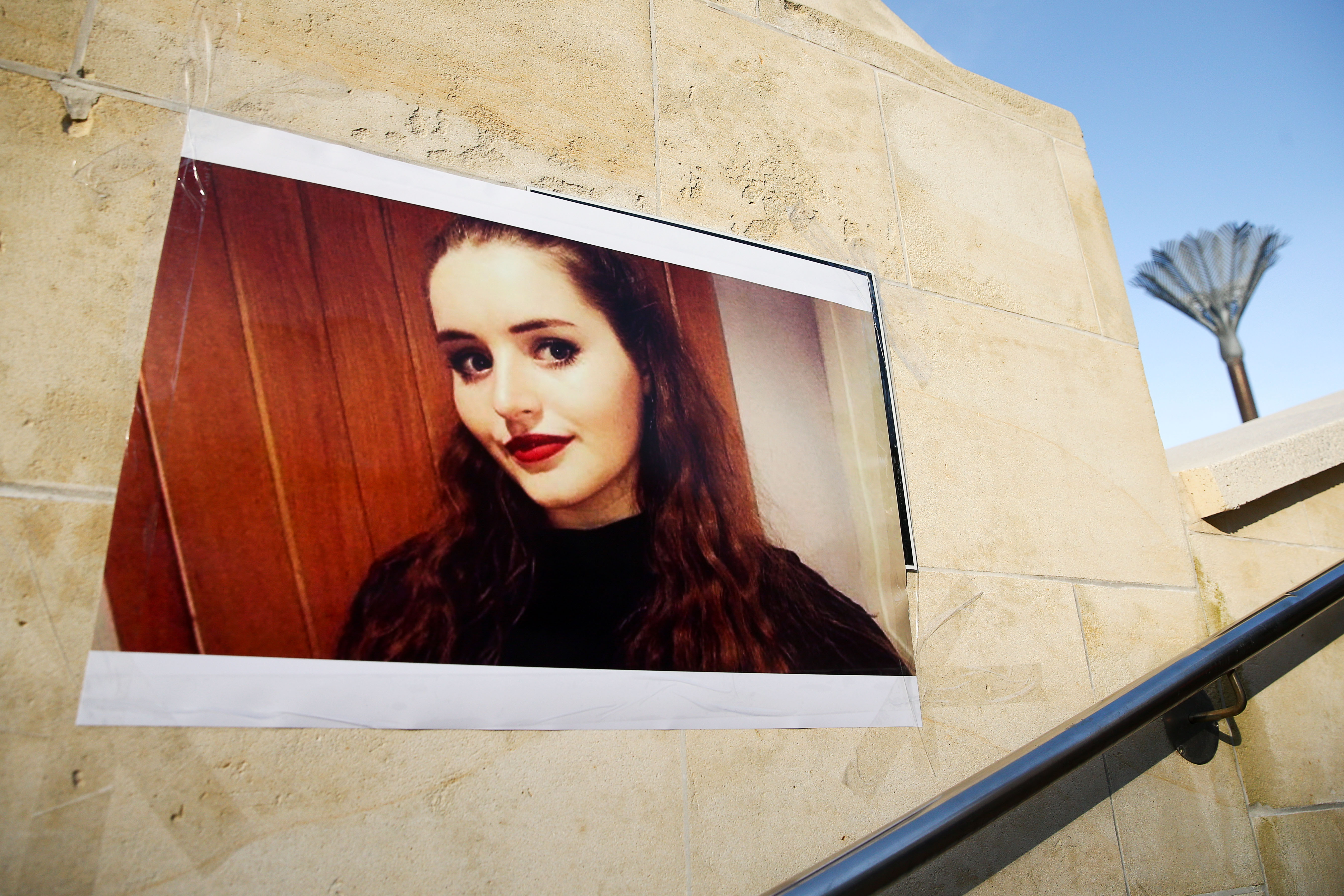 A photo of Grace Millane on the side of a building.