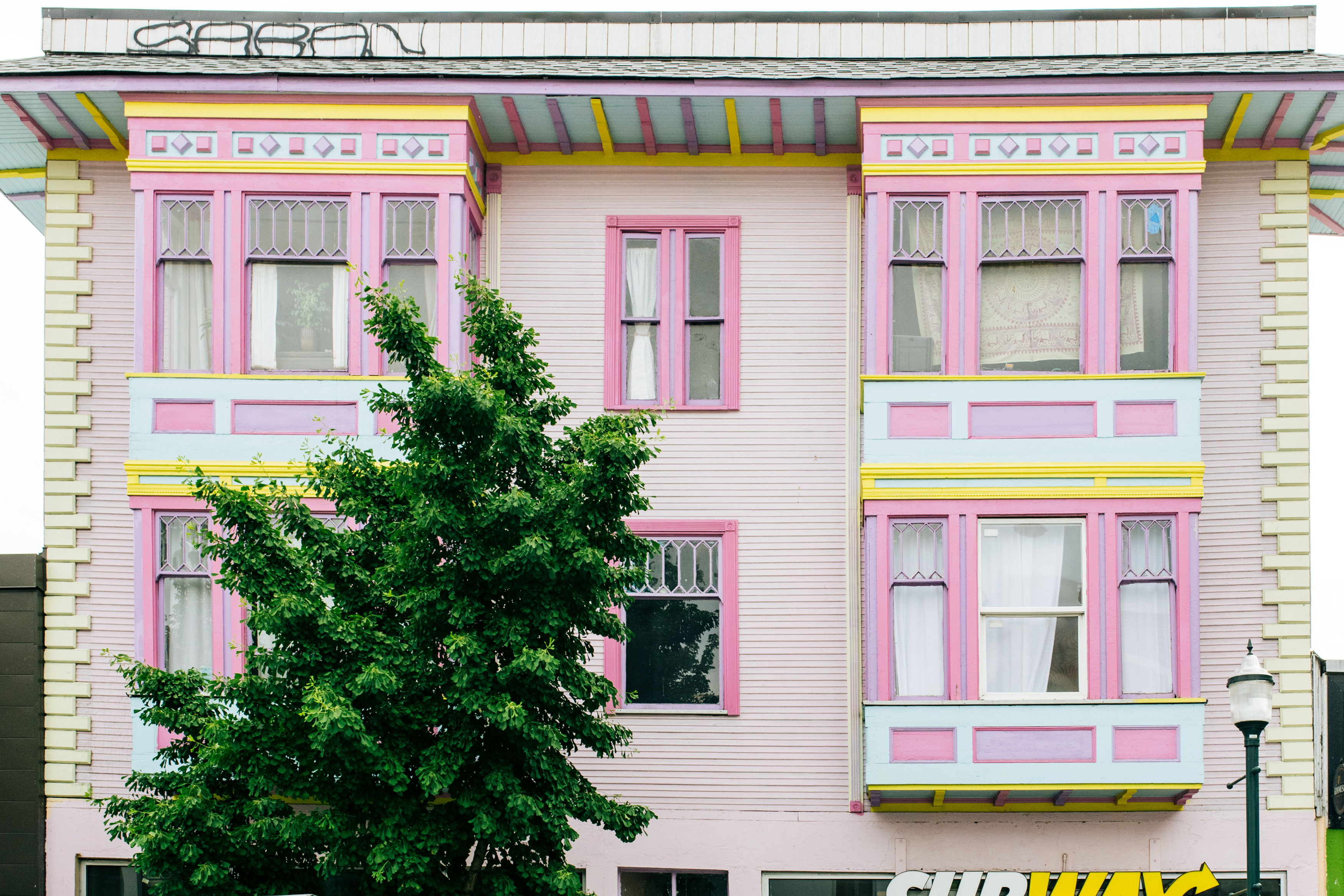 A pink apartment building with two-story bay windows on either side. The trim is colorful, with darker pink, light blue, and yellow elements.