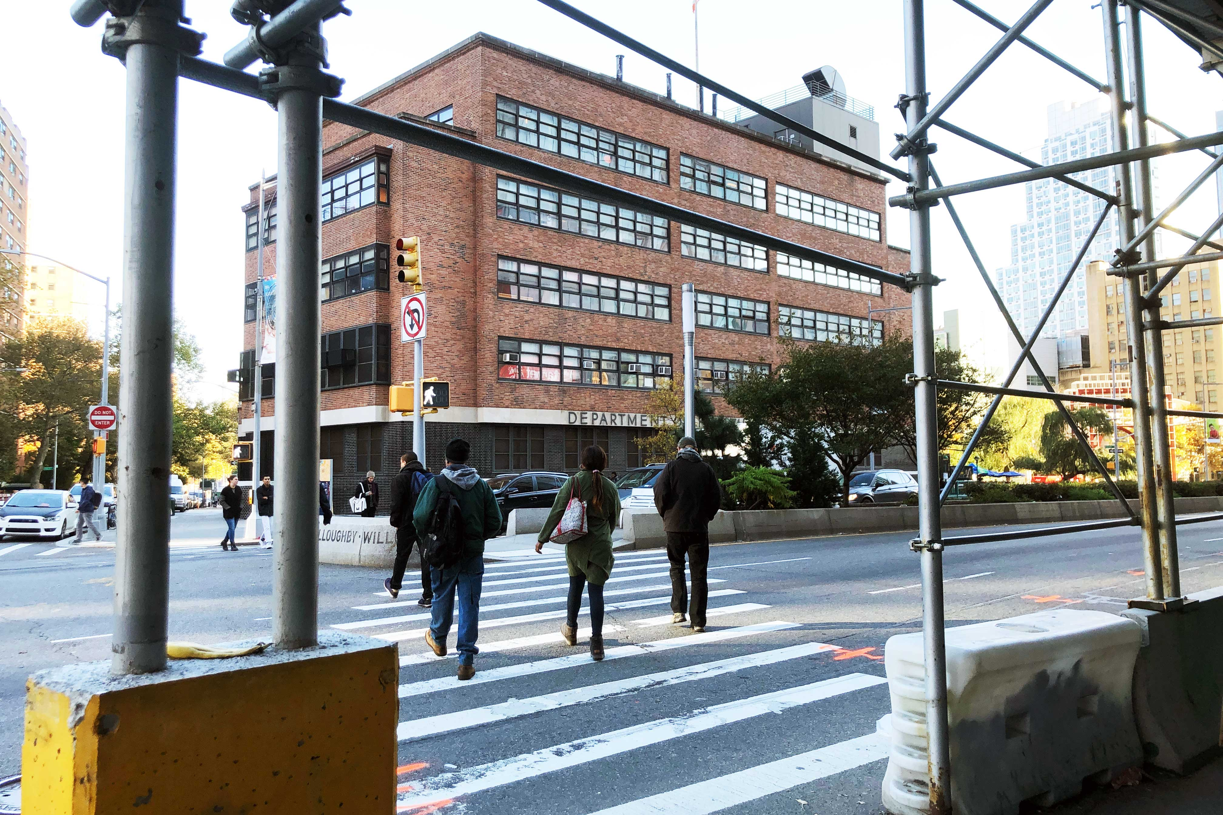 The building housing the Public Health Solutions clinic, with people crossing Flatbush Ave. in front of it.