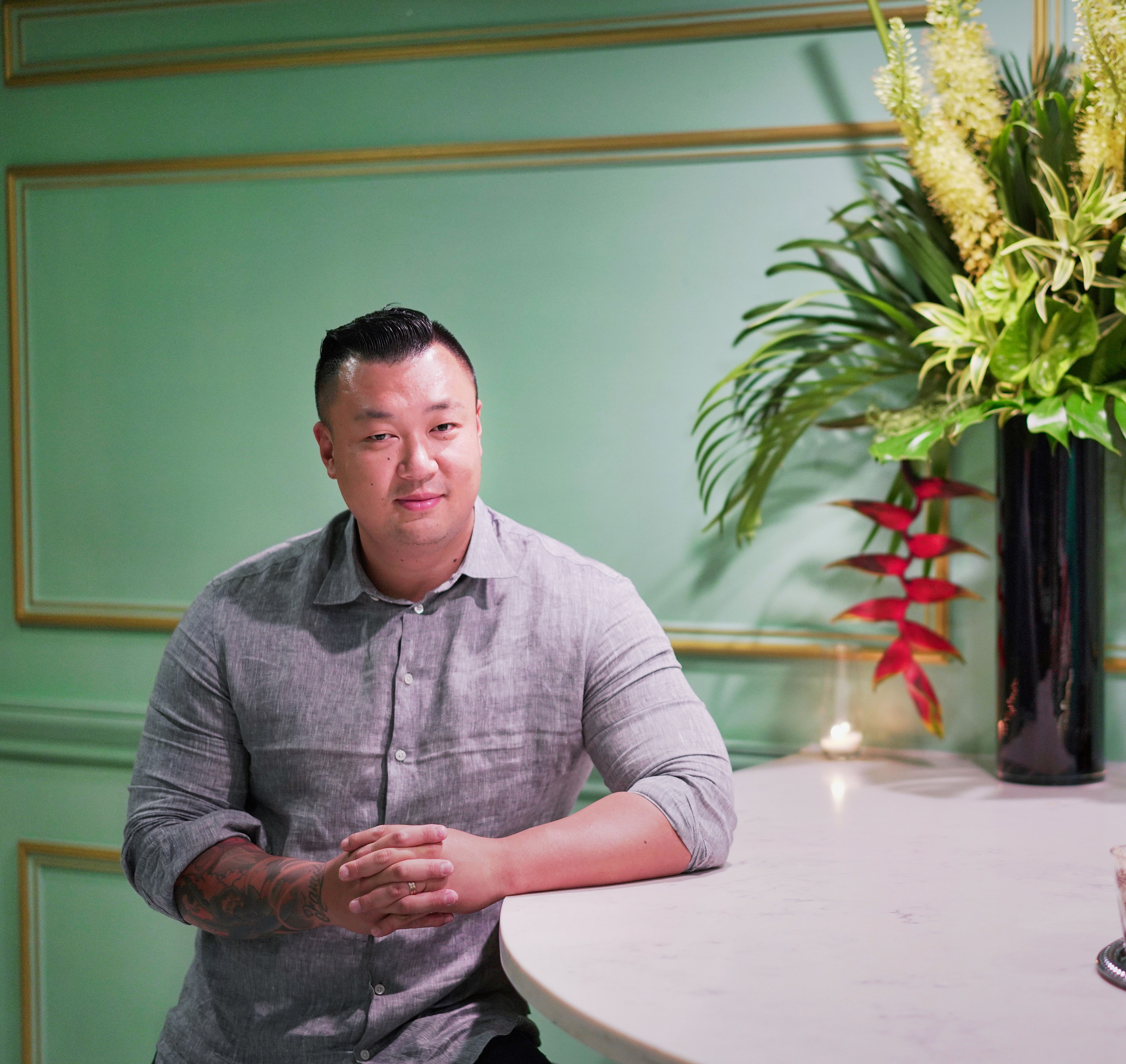A man stands against a white marble bar, looking at the camera. There are tropical plants to his right and a mint green wall behind him.