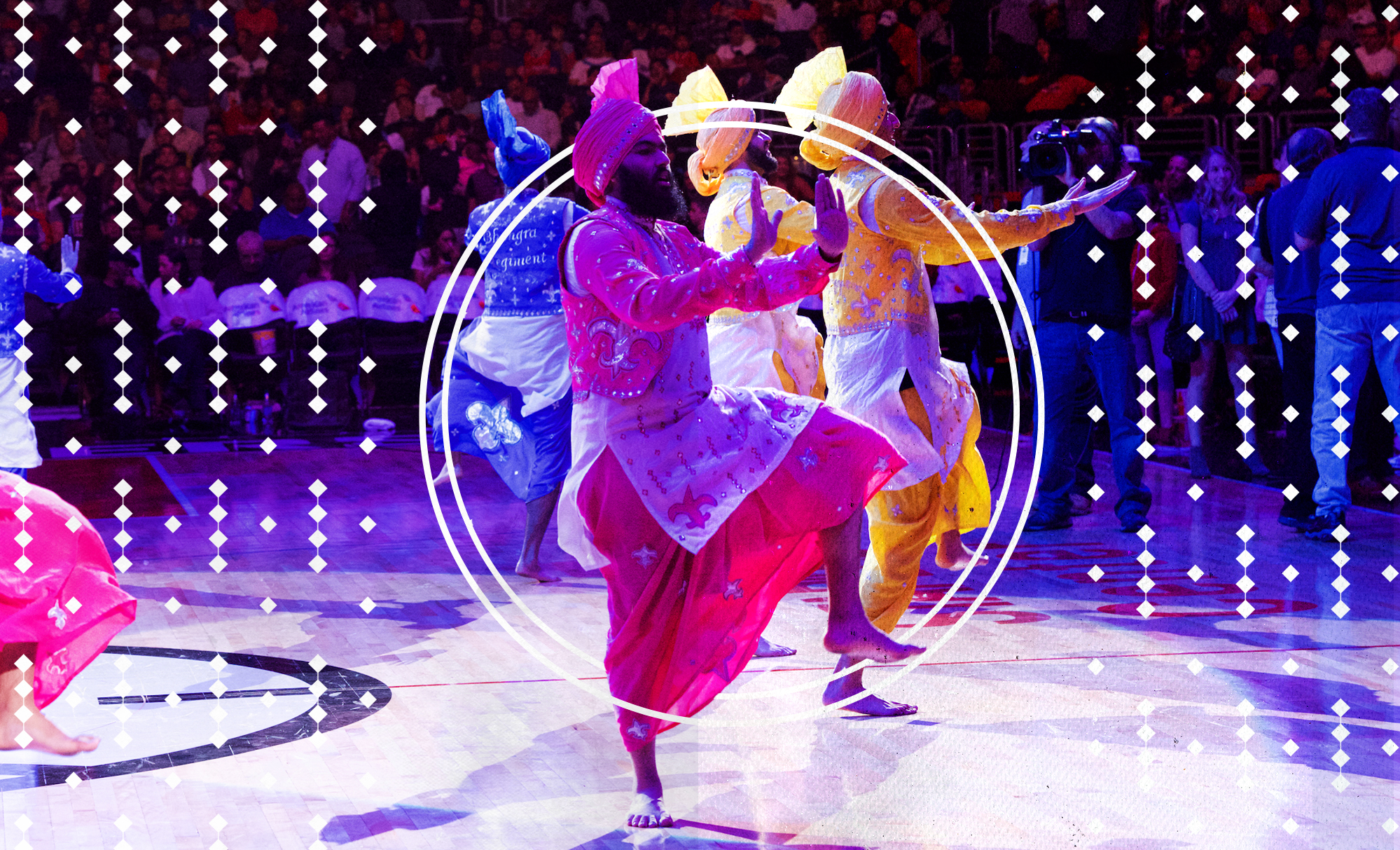 A Sikh man in pink-colored traditional clothing dancing on the home court of the Los Angeles Clippers as part of a group of Sikh dancers.