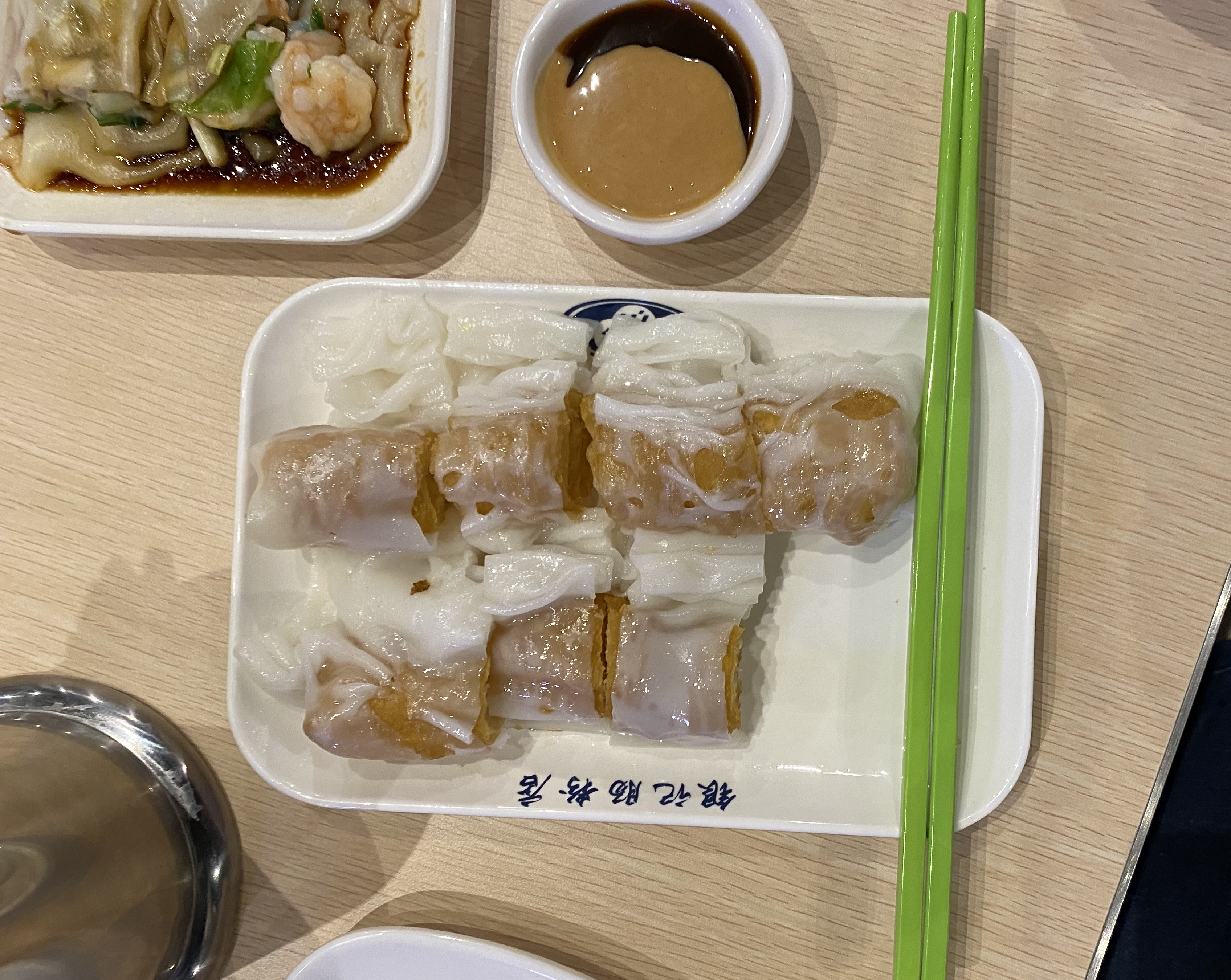 The youtiao cruller rice roll at Yin Ji Chang Fen sits on a white plate, adjacent a shrimp rice roll.
