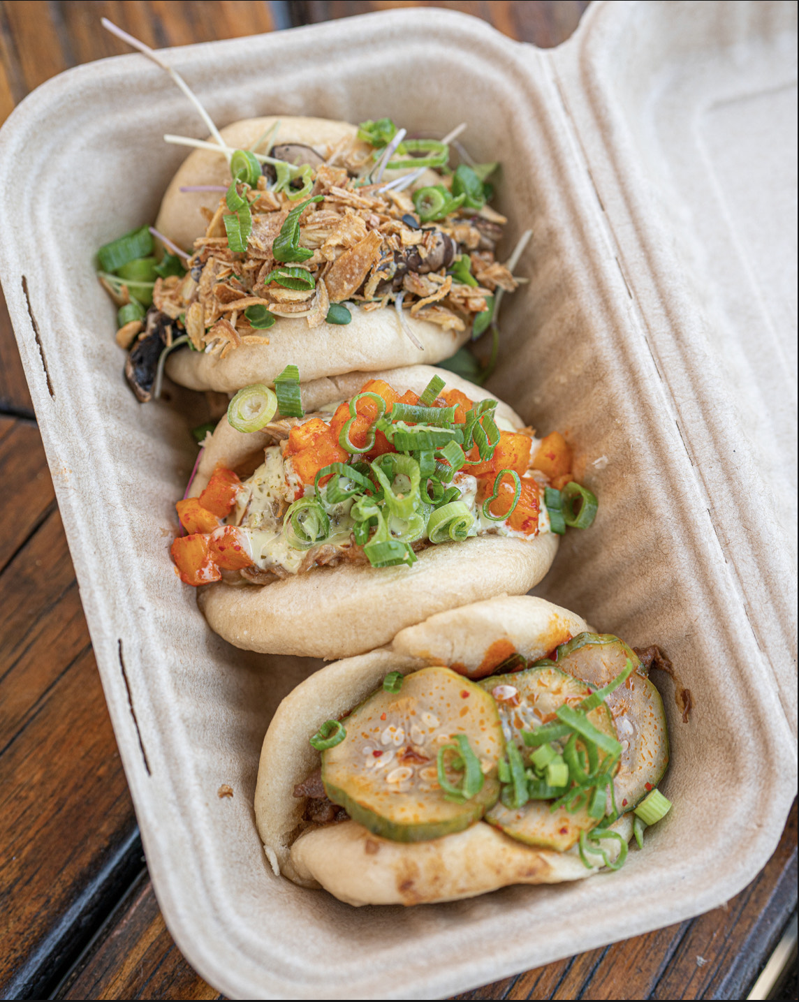 A takeout tray with mushroom, pork belly, and Korean barbecue beef buns from Bun's Up.