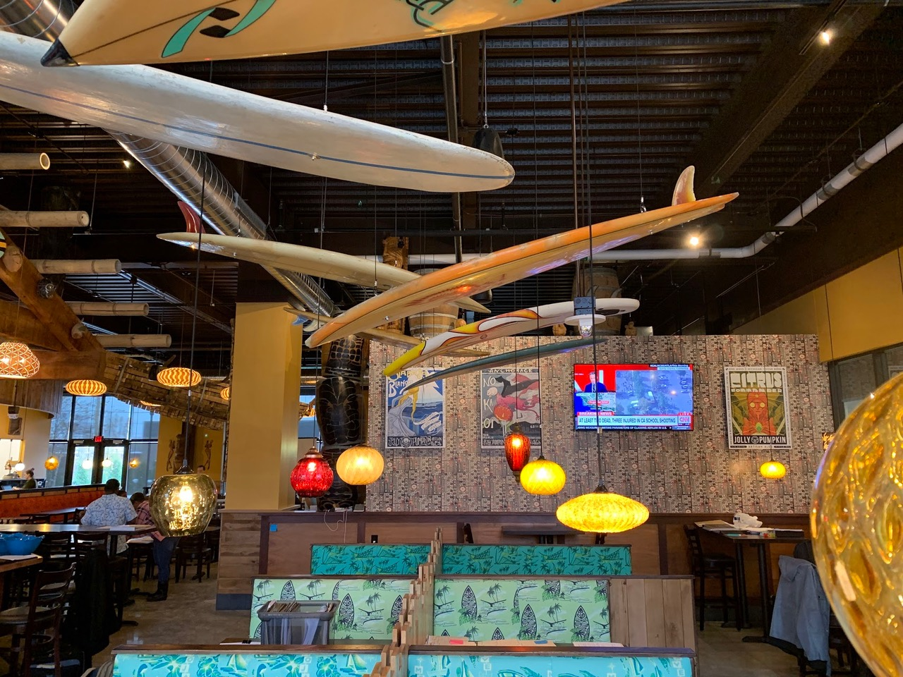 A dining room with surfboards hanging from the ceiling.