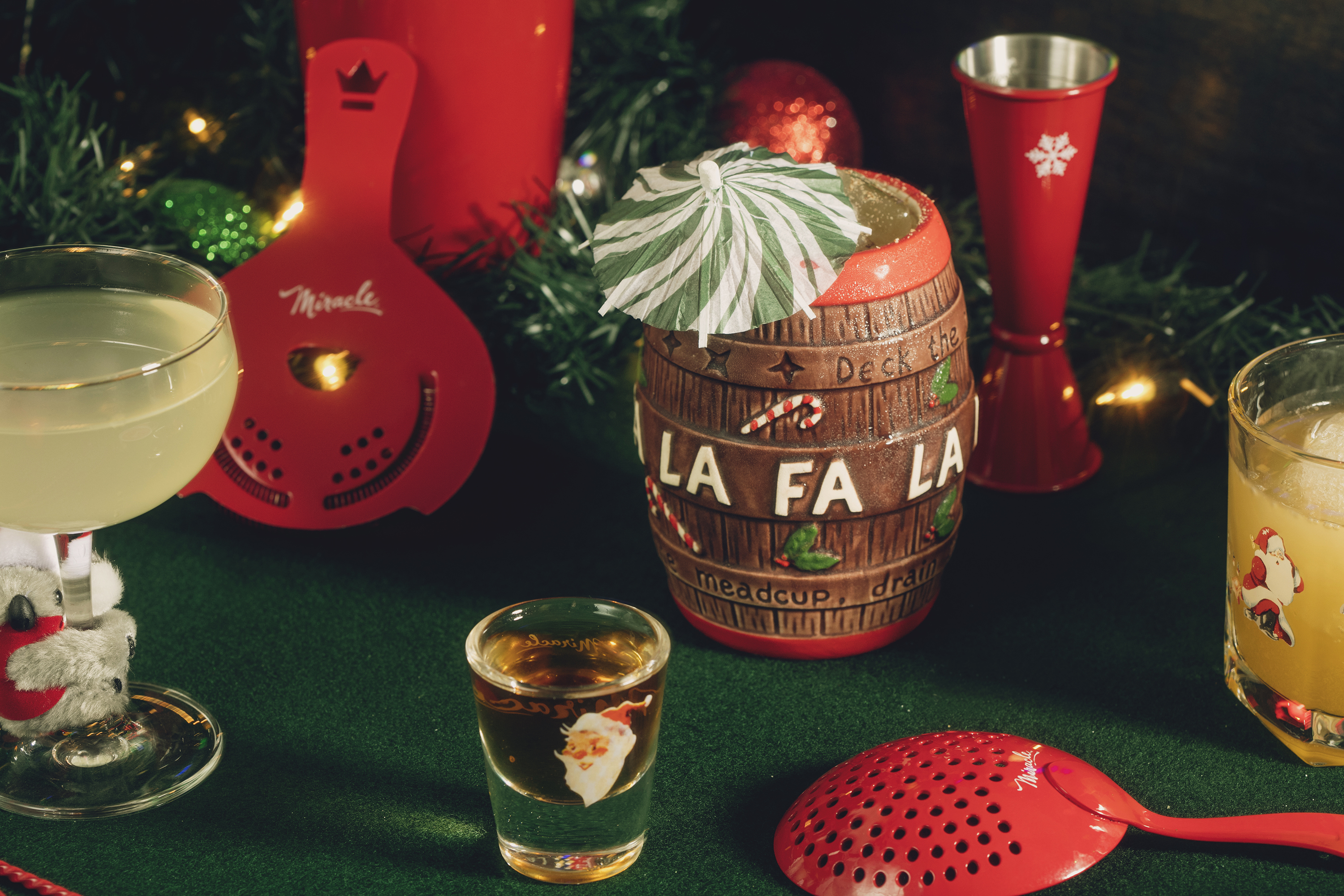 """A holiday-themed tableau includes a mug shaped like a barrel that says """"Fa-La-La"""" with a cocktail umbrella, a Santa shot glass, and red cocktail mixing tools."""