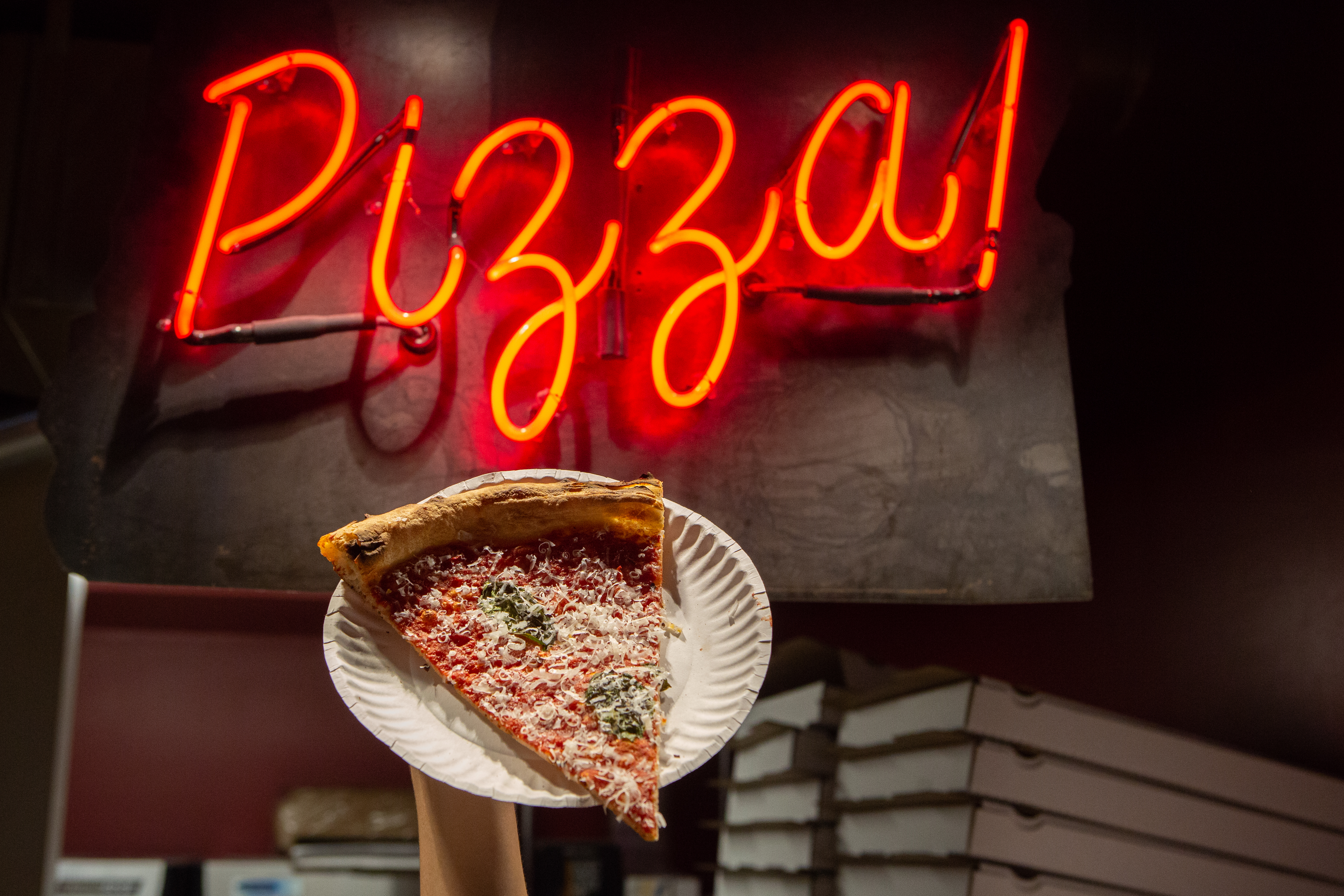 """A hand holds up a slice of marinara pizza on a paper plate in front of Checkerboard's neon """"Pizza!"""" sign"""
