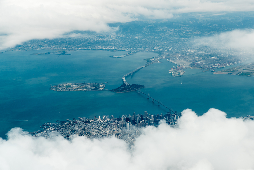 An aerial photo of an island surrounded by blue bay waters on all sides, with bridges connecting to dense cities on the north and south sides and clouds in the foreground.