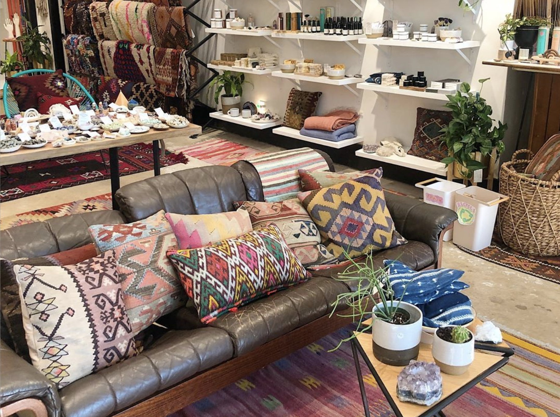 A leather couch with lots of throw pillows. A triangular side table has ceramic planters. The shop has rugs hanging in the back with shelves that have ceramics.