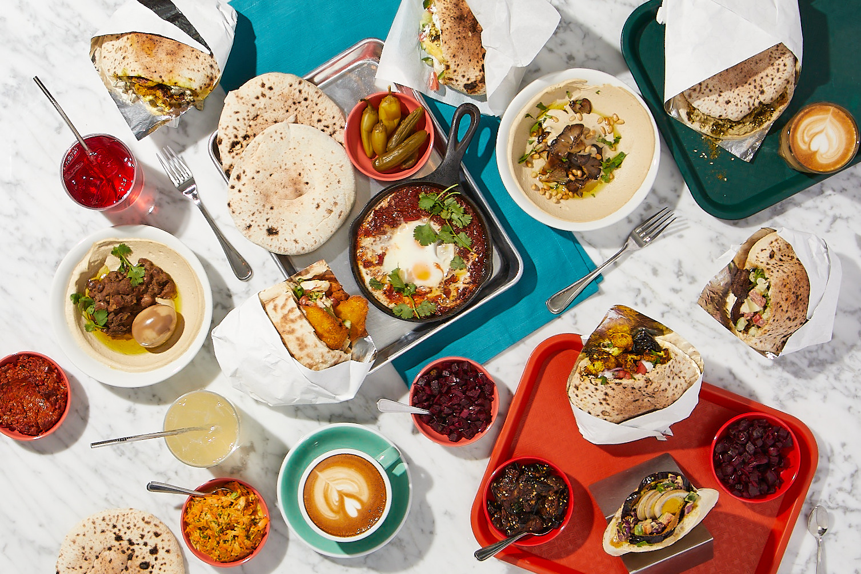 trays with pita sandwiches, coffee, and salatim