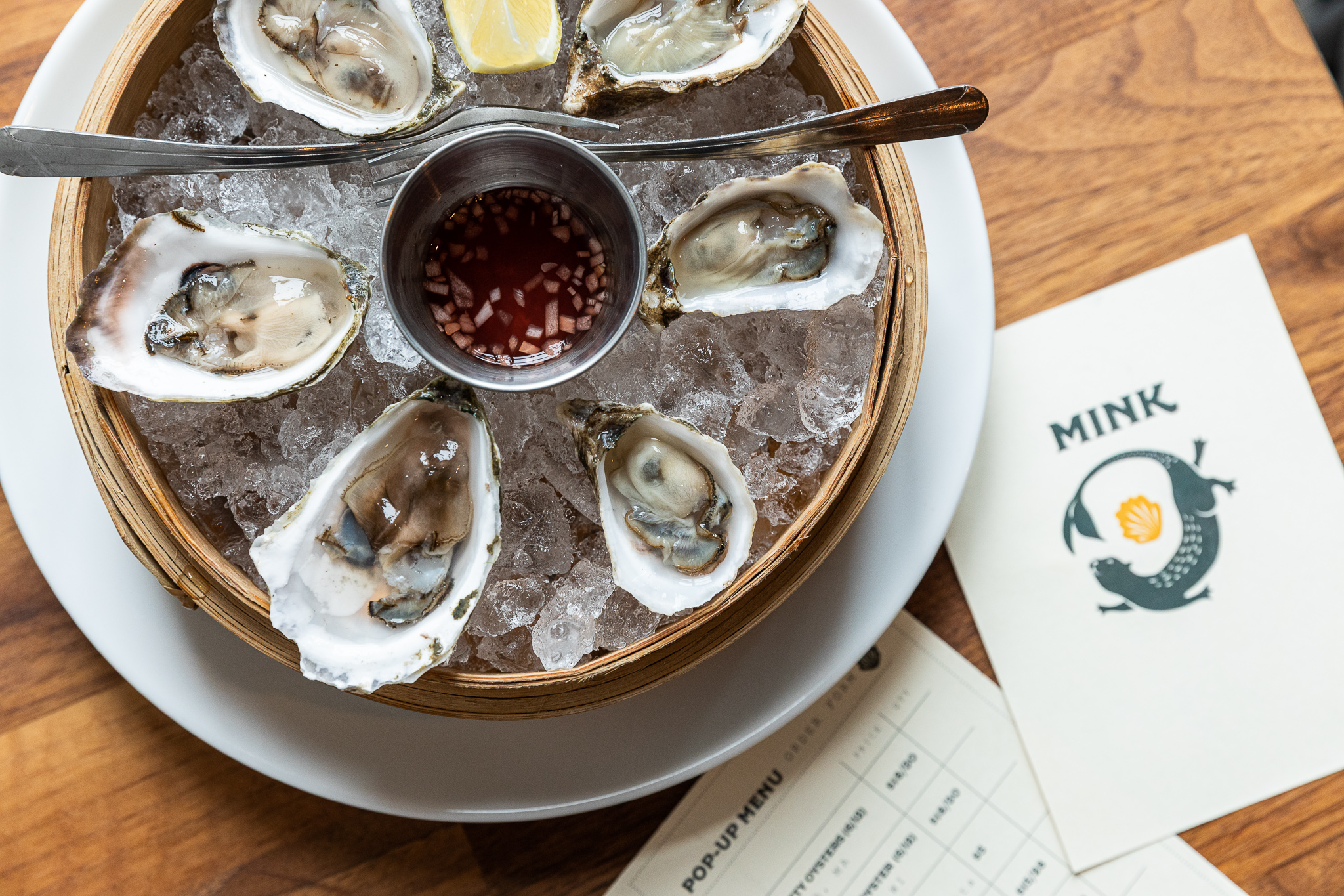 A tray of oysters on ice next to a menu for Mink.