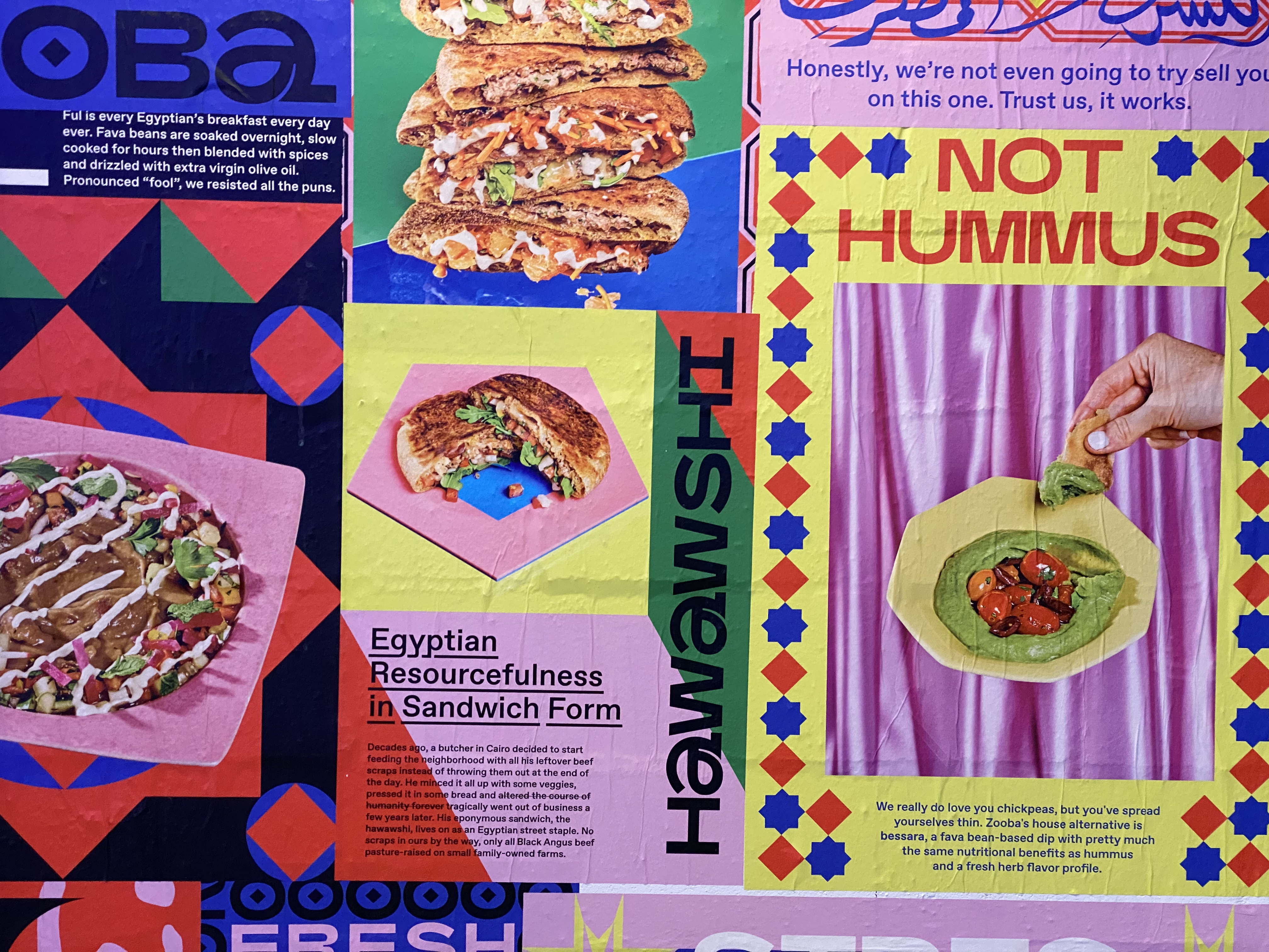 Polychromatic posters display the signature hawawshi and ful offerings at Zooba