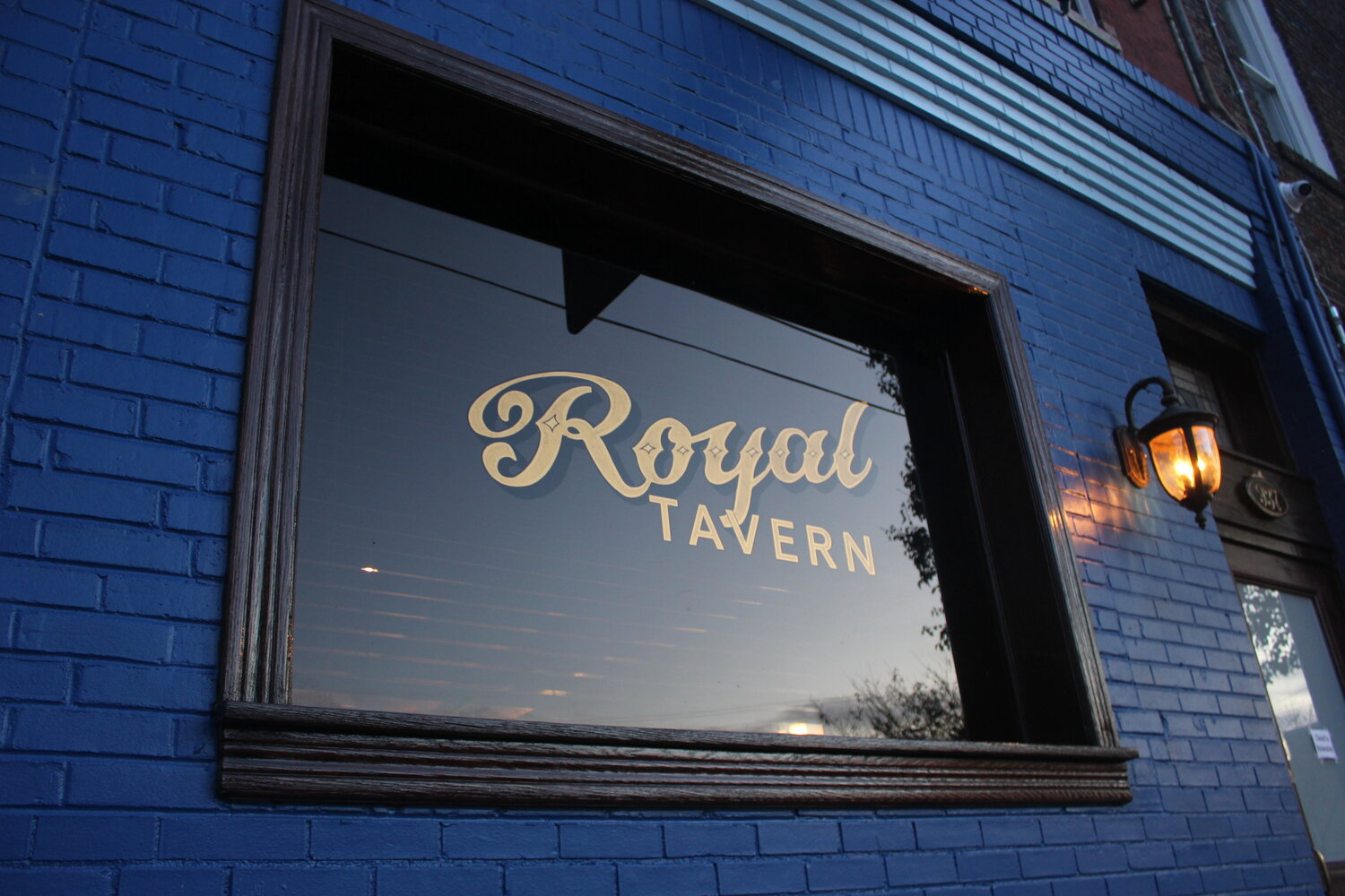 blue exterior of bar with sign in window that says royal tavern