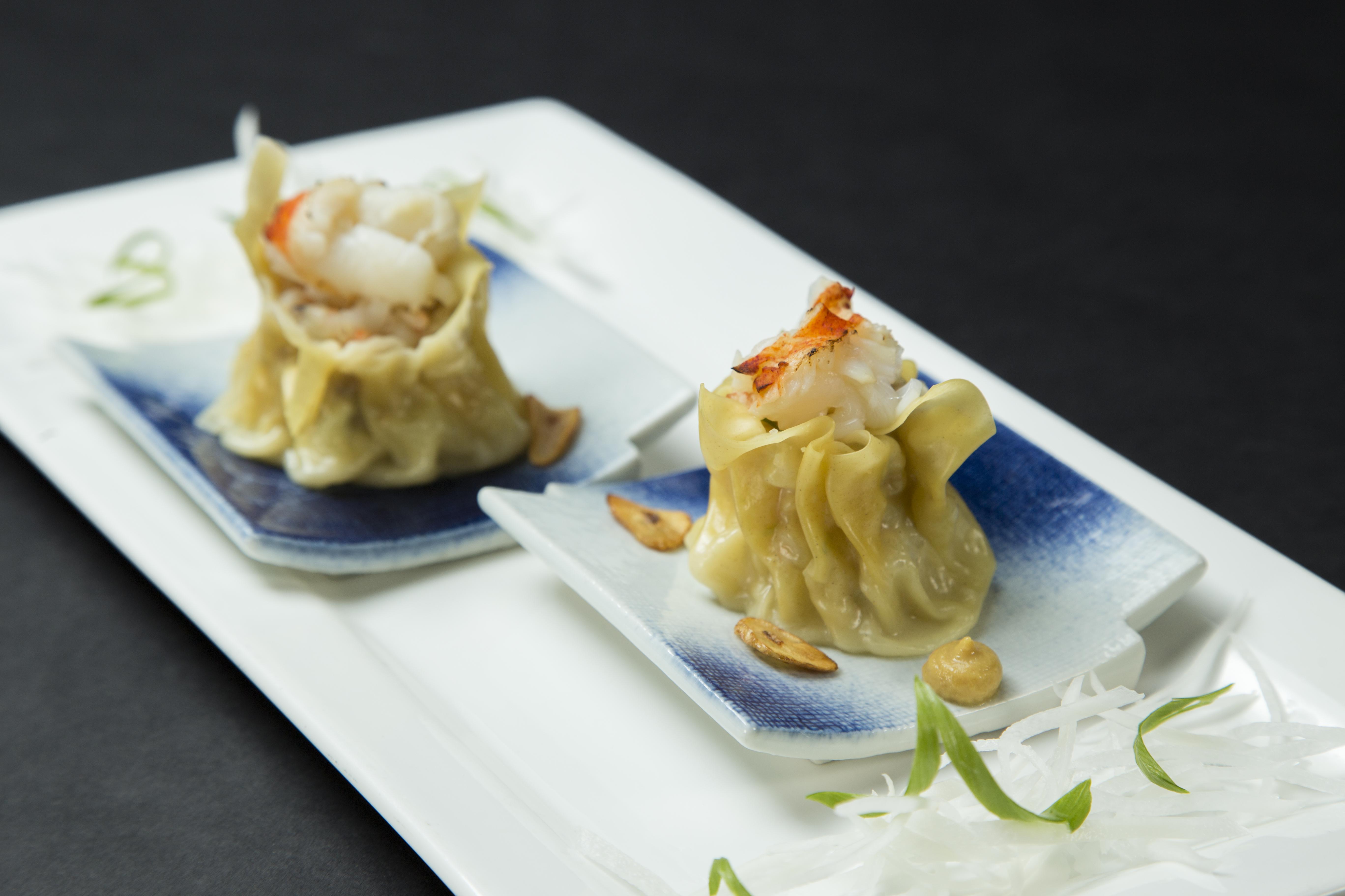 Two steamed dumplings on a plate.