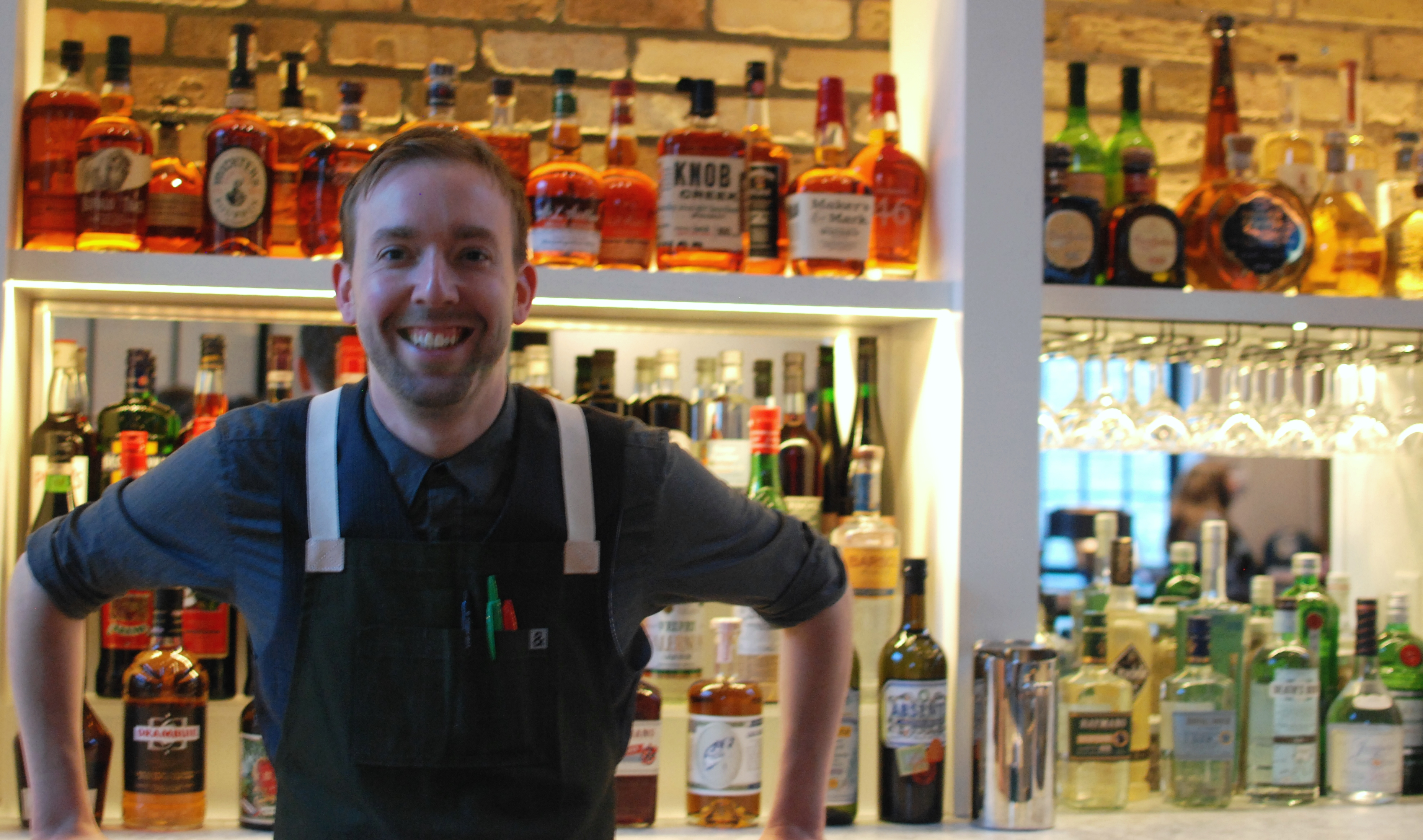 Robb Jones in an apron smiling behind a bar
