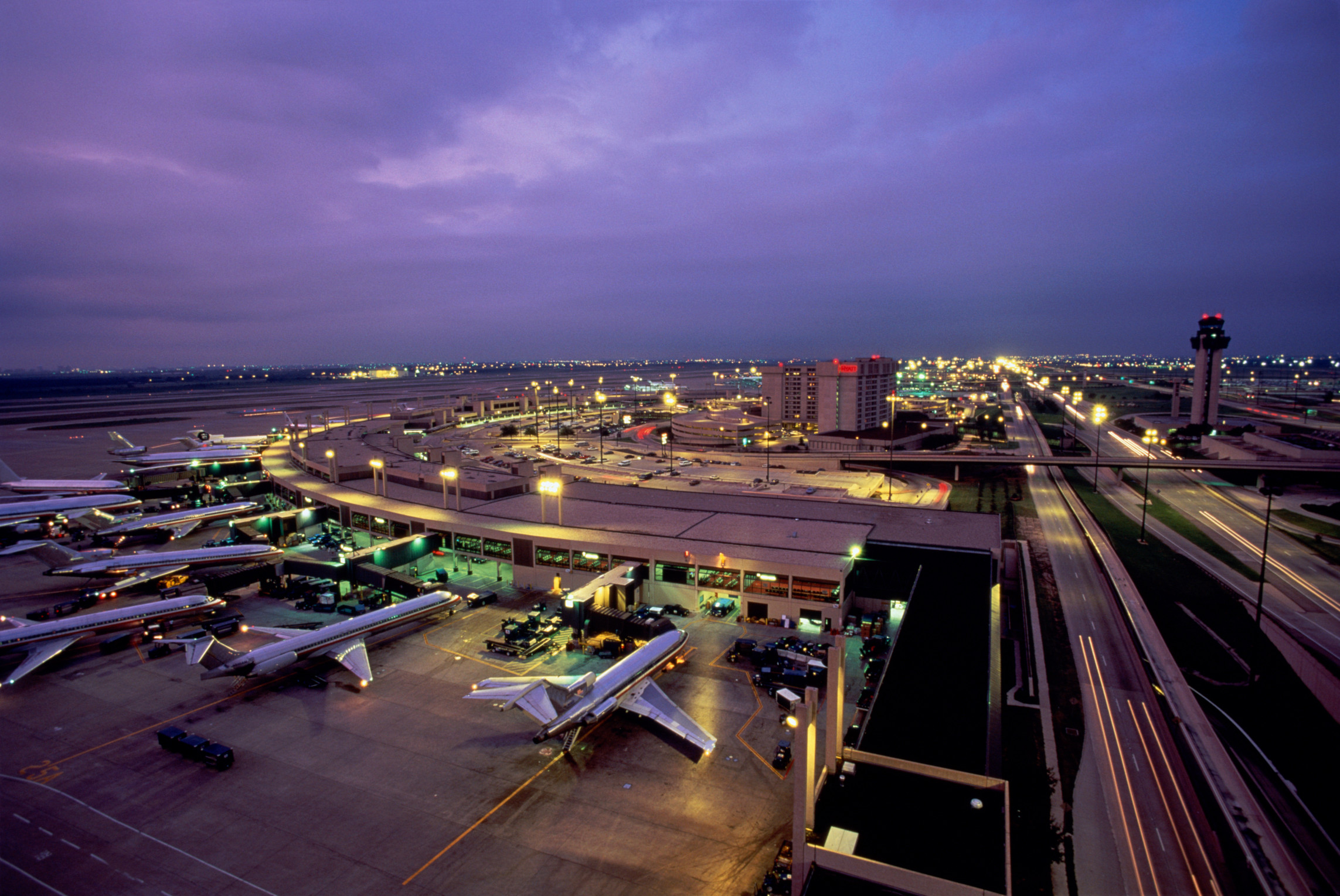 A massive airport terminal at dusk is seen from above, with dozens of jets parked at gates illuminated with an array of glowing lights against a darkening sky.