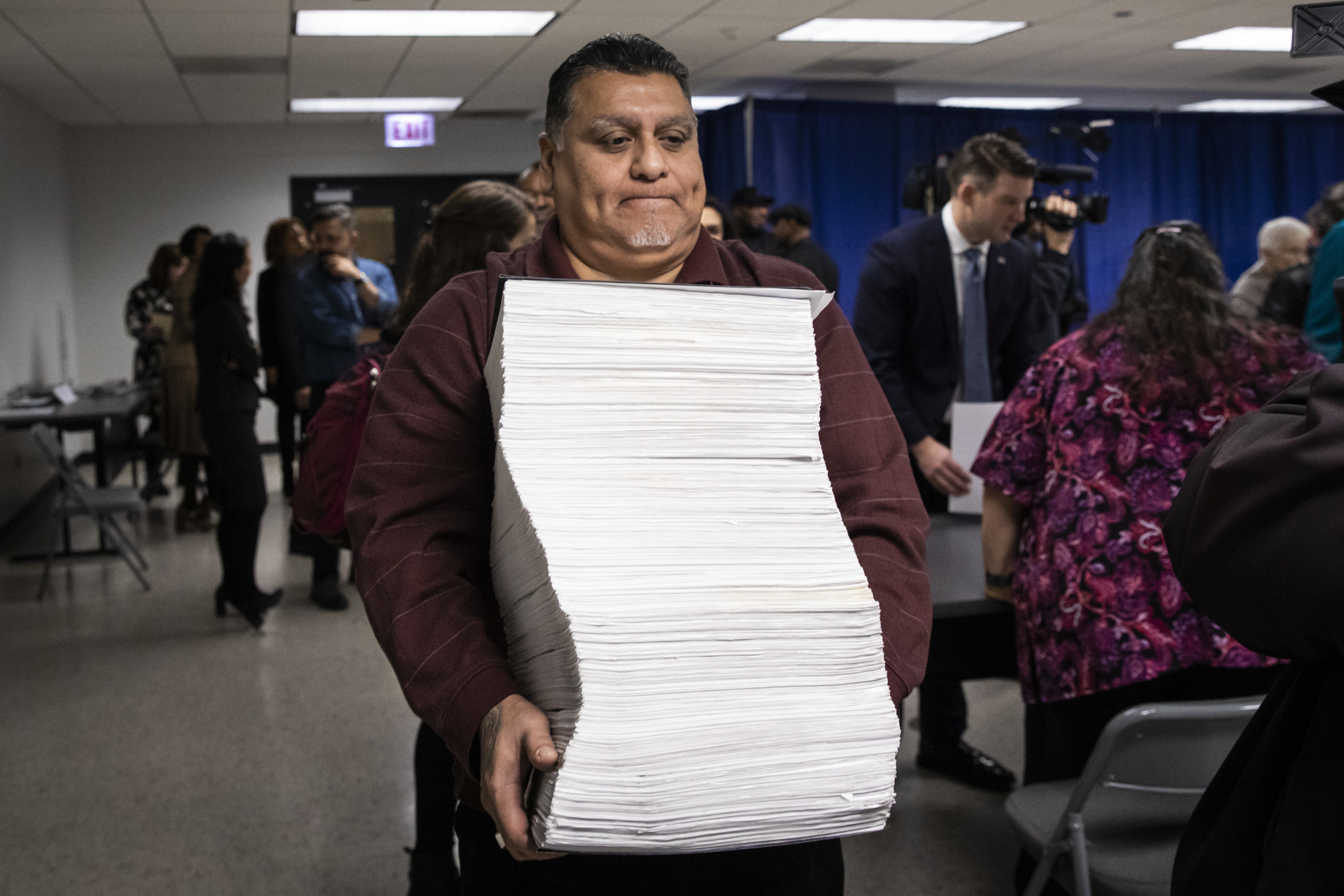Rito Medellin, an employee in the Cook County Clerk's office, carries the nominating petitions for Bill Conway, a candidate for Cook County state's attorney.
