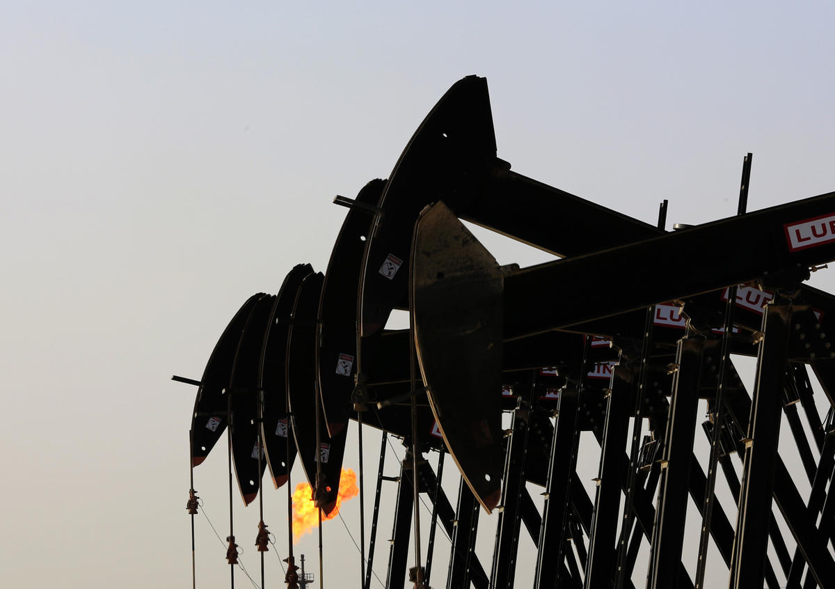 Oil pumps work in front of a gas flame in the desert oil fields of Sakhir, Bahrain, Thursday, May 28, 2015.