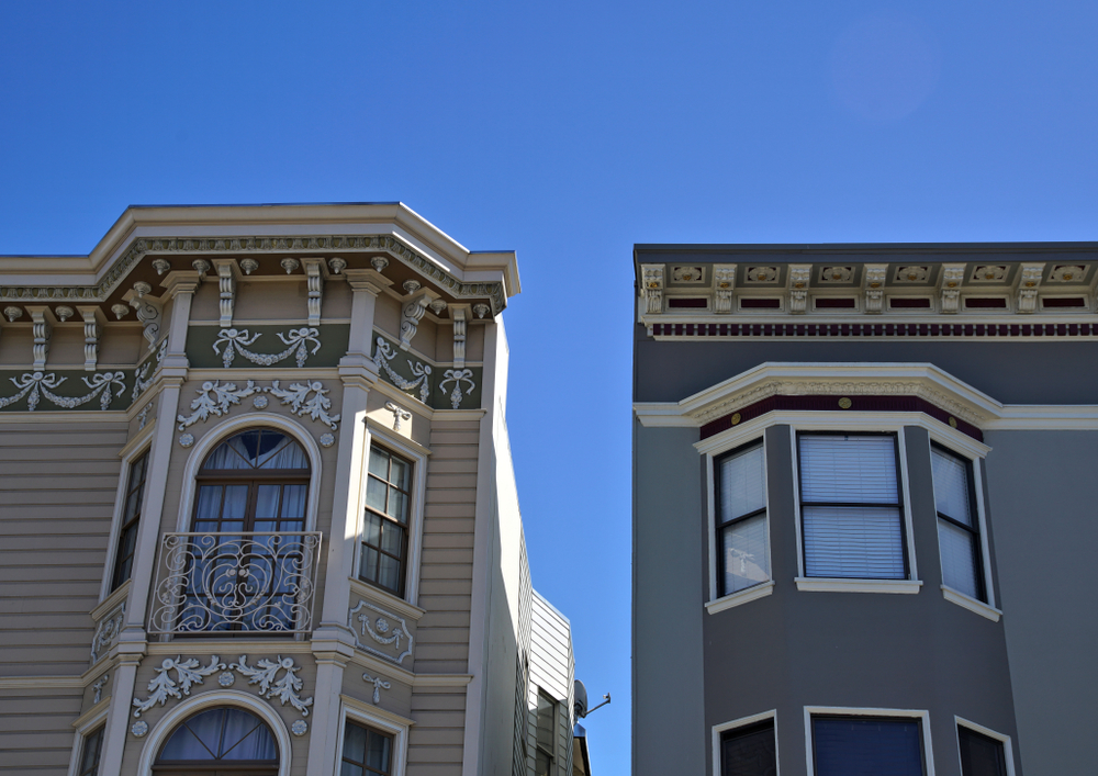 Two San Francisco apartment building side by side; the one on the left is more baroque, the one on the right more plain.