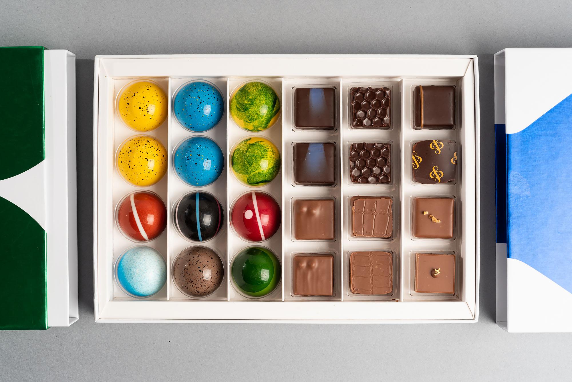 Colorful bitesized chocolates in a white box.