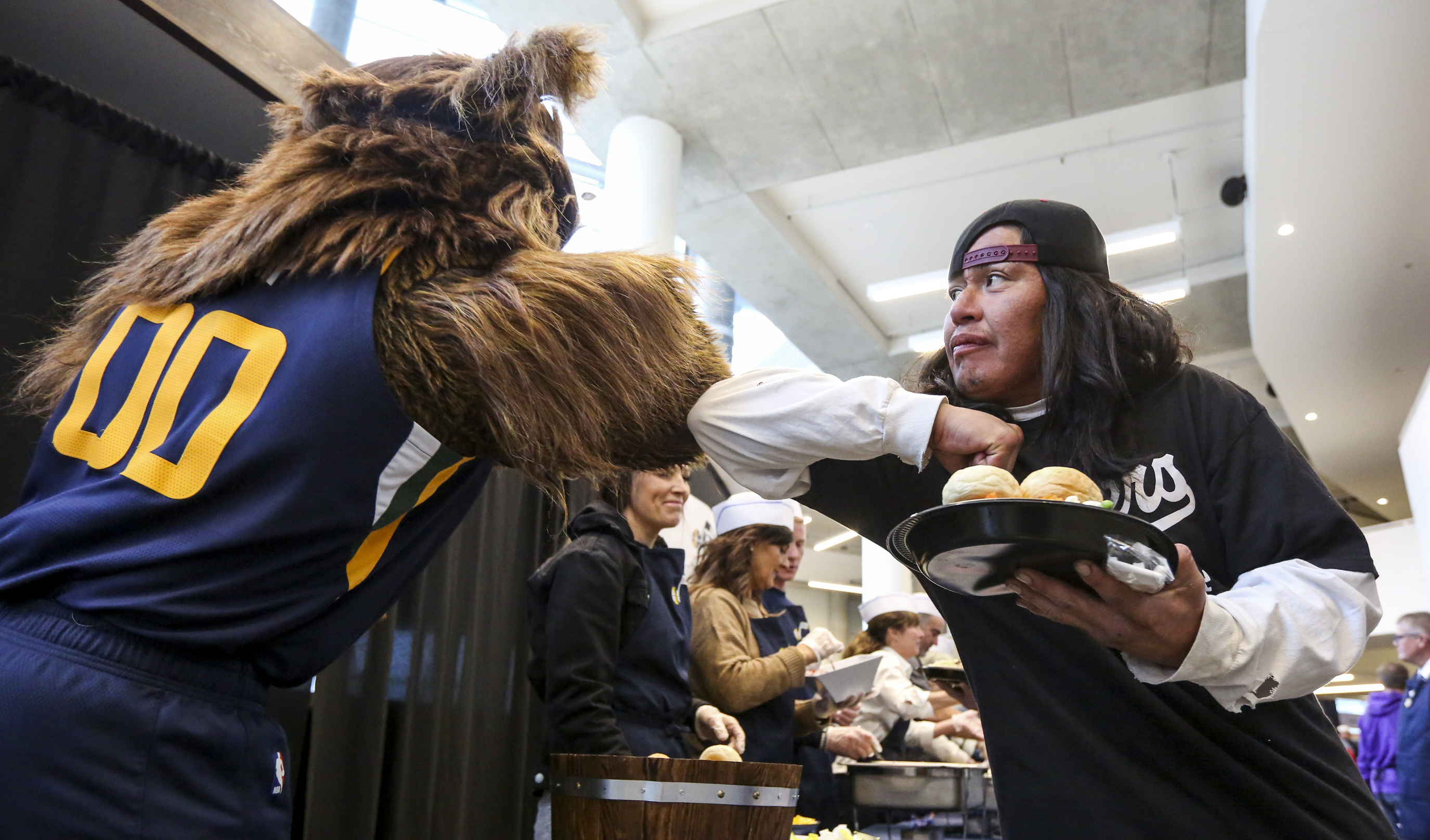 """Julian, right, bumps elbows with the Jazz Bear after receiving his Thanksgiving meal during the 21st annual """"We Care - We Share"""" event for the homeless and low-income individuals at the Vivint Smart Home Arena in Salt Lake City on Monday, Nov. 25, 2019. The Salt Lake Mission was also on hand to provide coats, shoes and cold-weather apparel to those in attendance."""