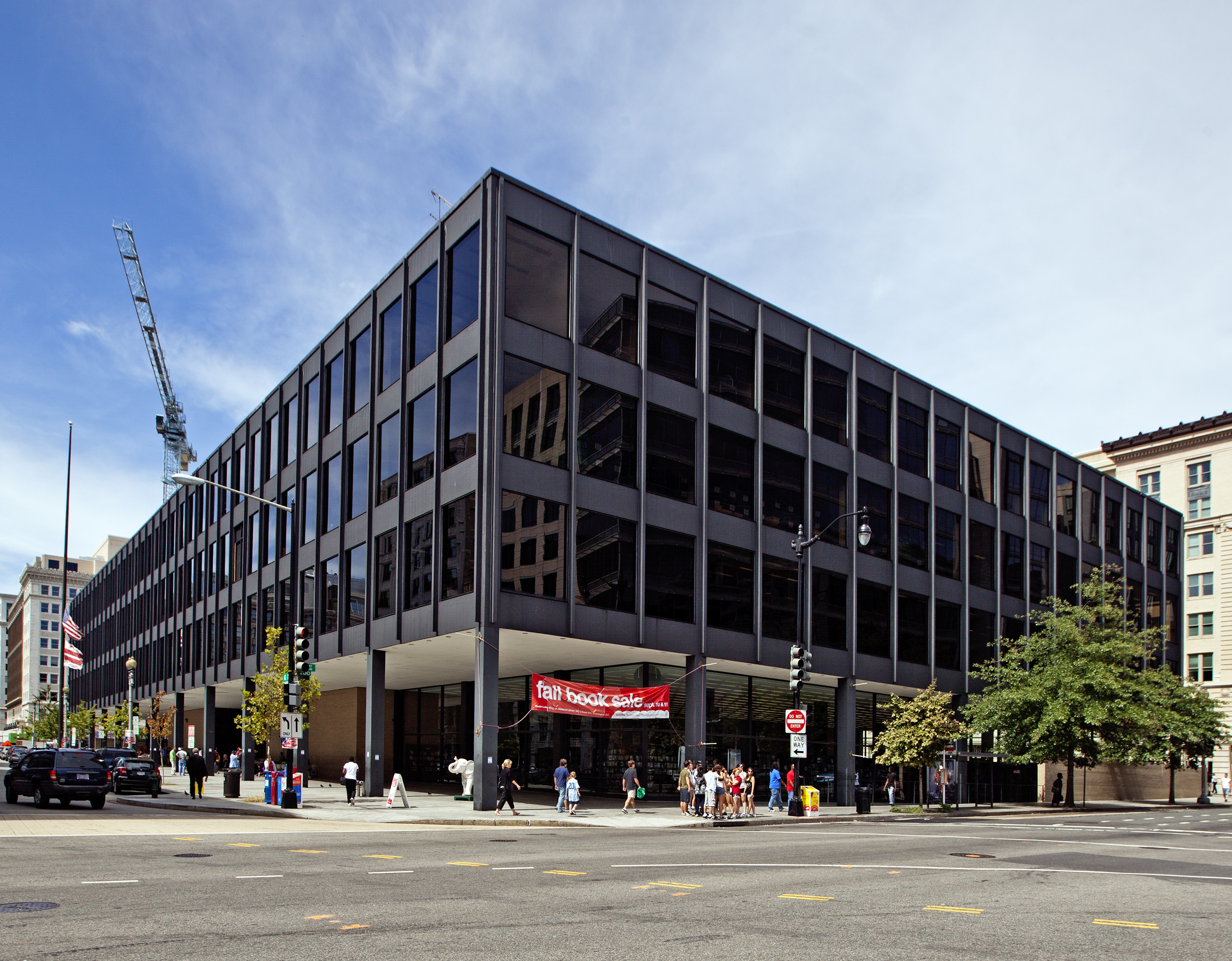 A modern library building on a city corner. The building is black and has large, occluded windows.