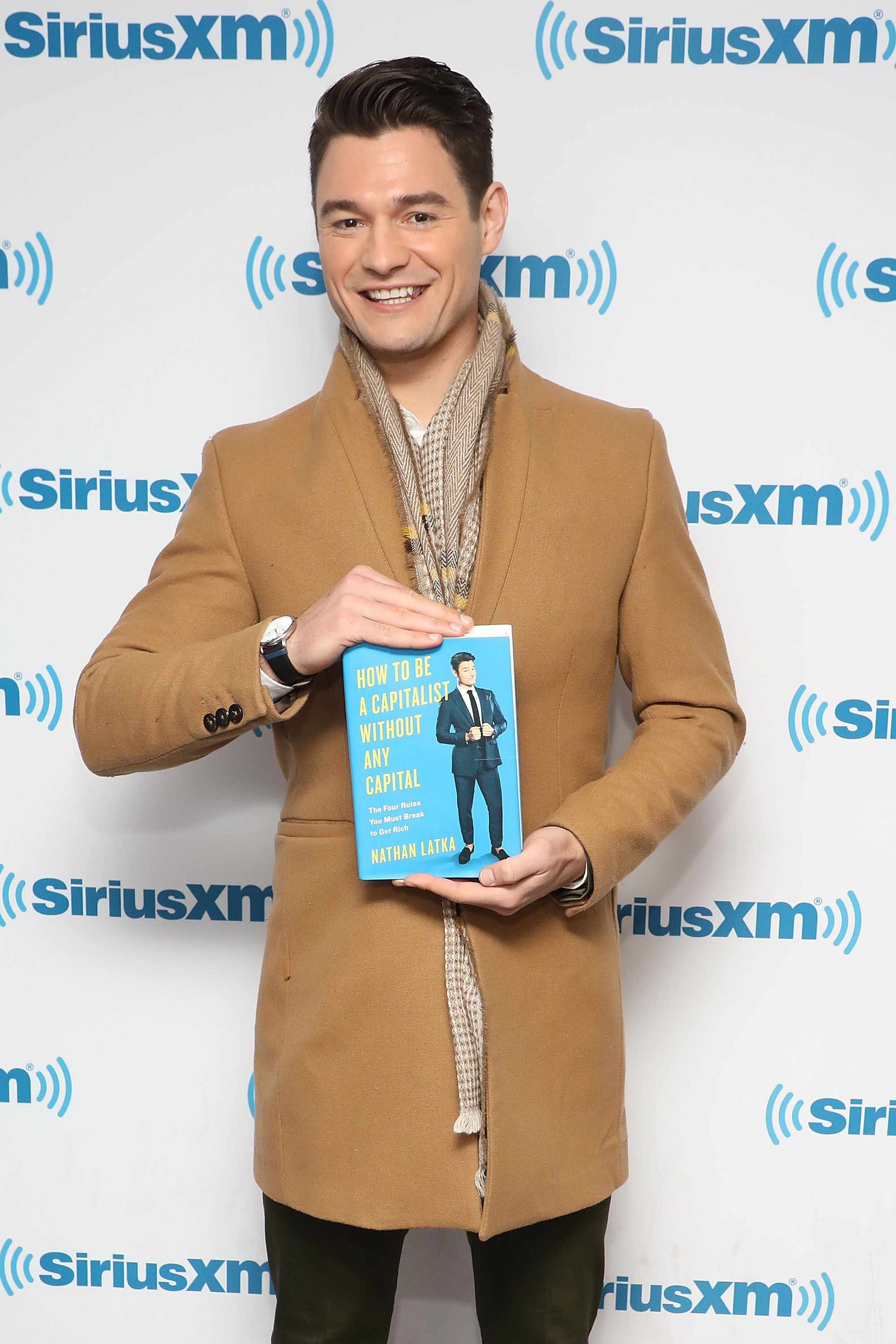 """Nathan Latka posing with his book """"How to Be a Capitalist Without Any Capital"""" at SiriusXM Studios."""